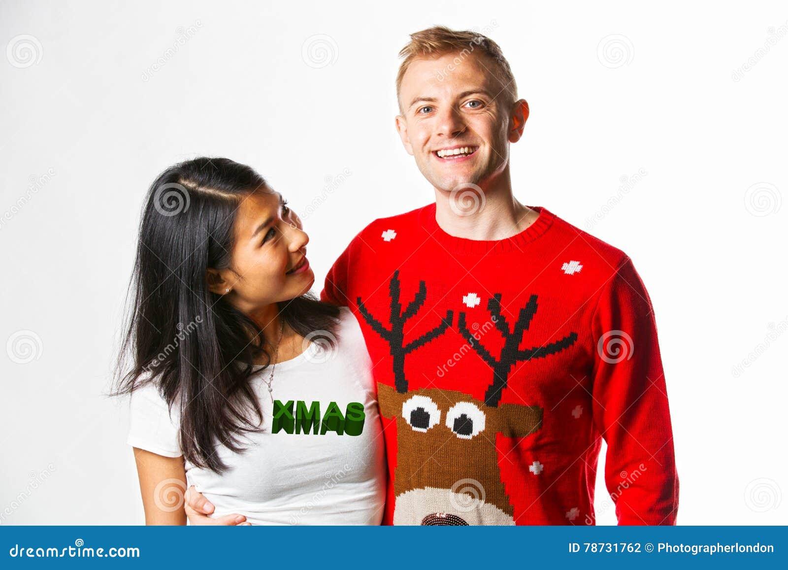 Stående av bärande julförkläden för lyckliga multietniska par i studiostunden som ser de