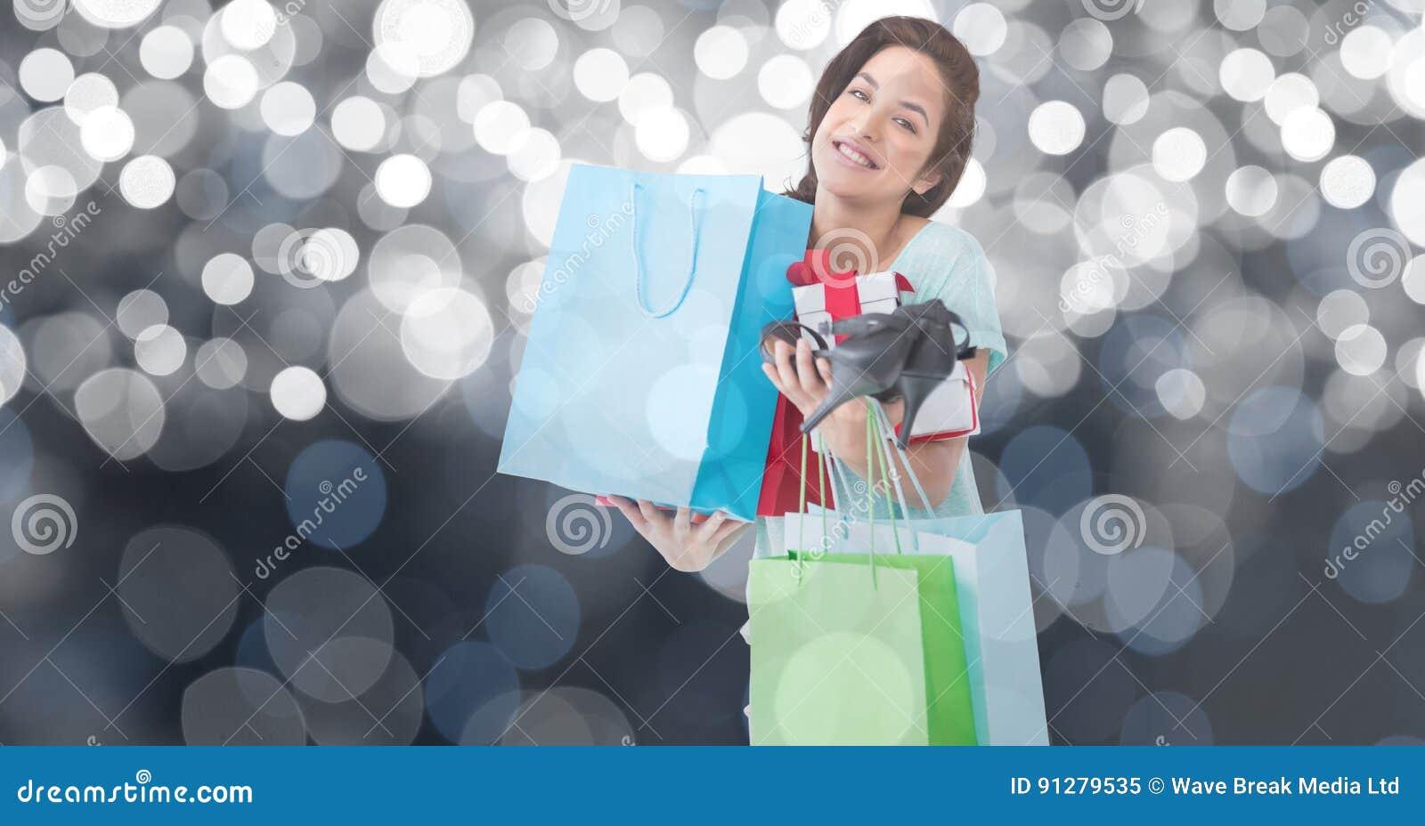 Stående av bärande shoppingpåsar för kvinna och höga häl mot bokeh