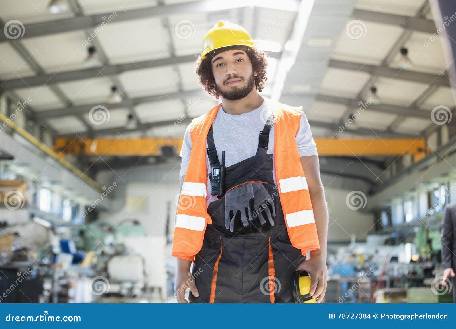 Stående av bärande skyddskläder för ung man i metallbransch