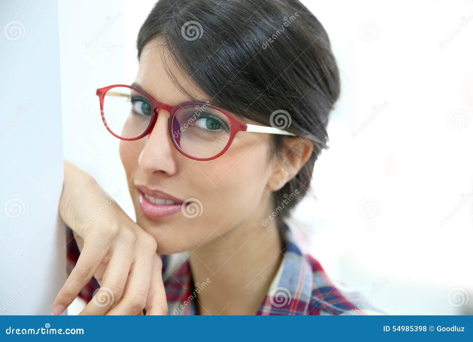 Stående av benägenheten för ung kvinna på väggen