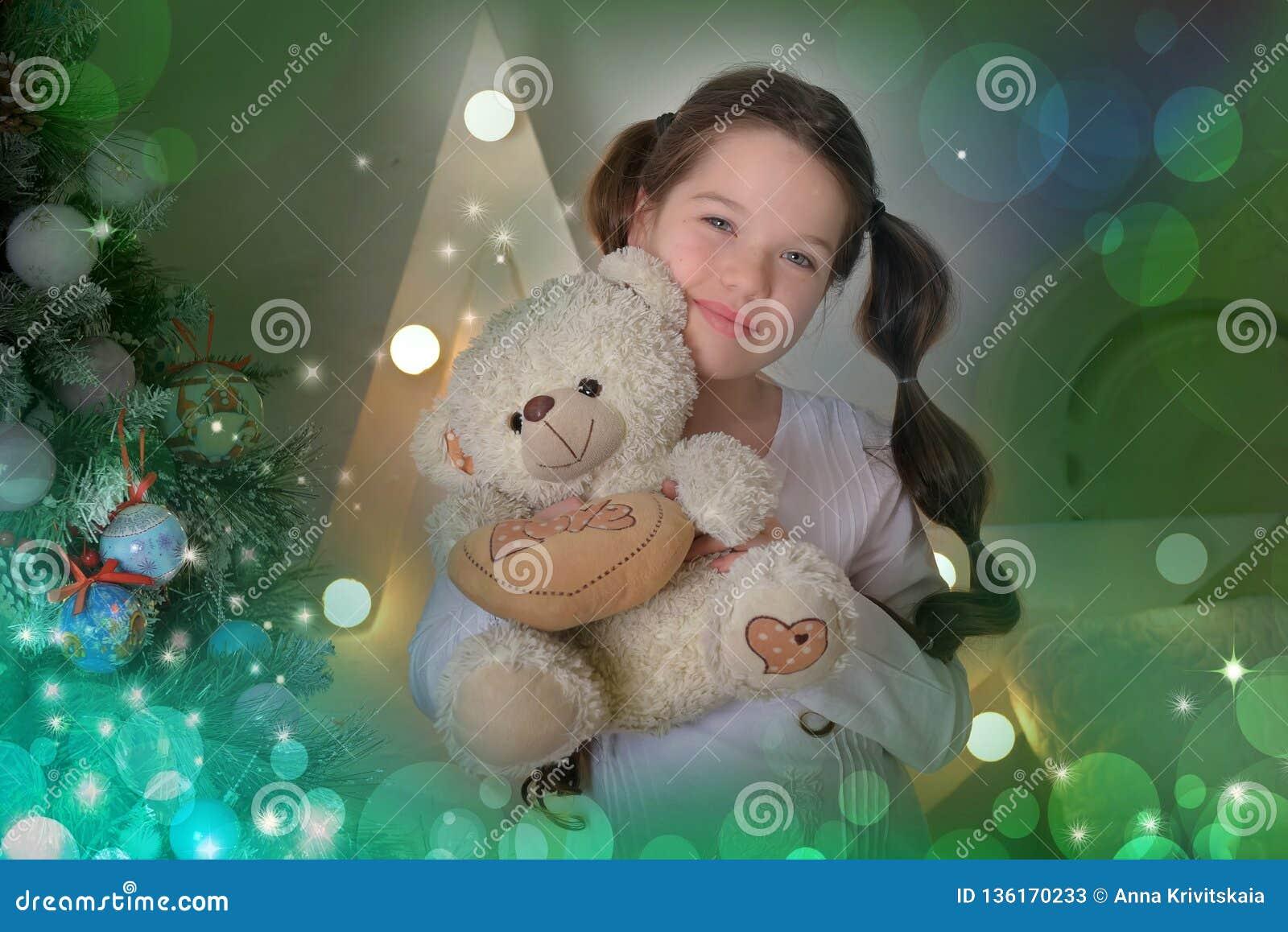 Stående av brunettflickan med nallebjörnen i hand