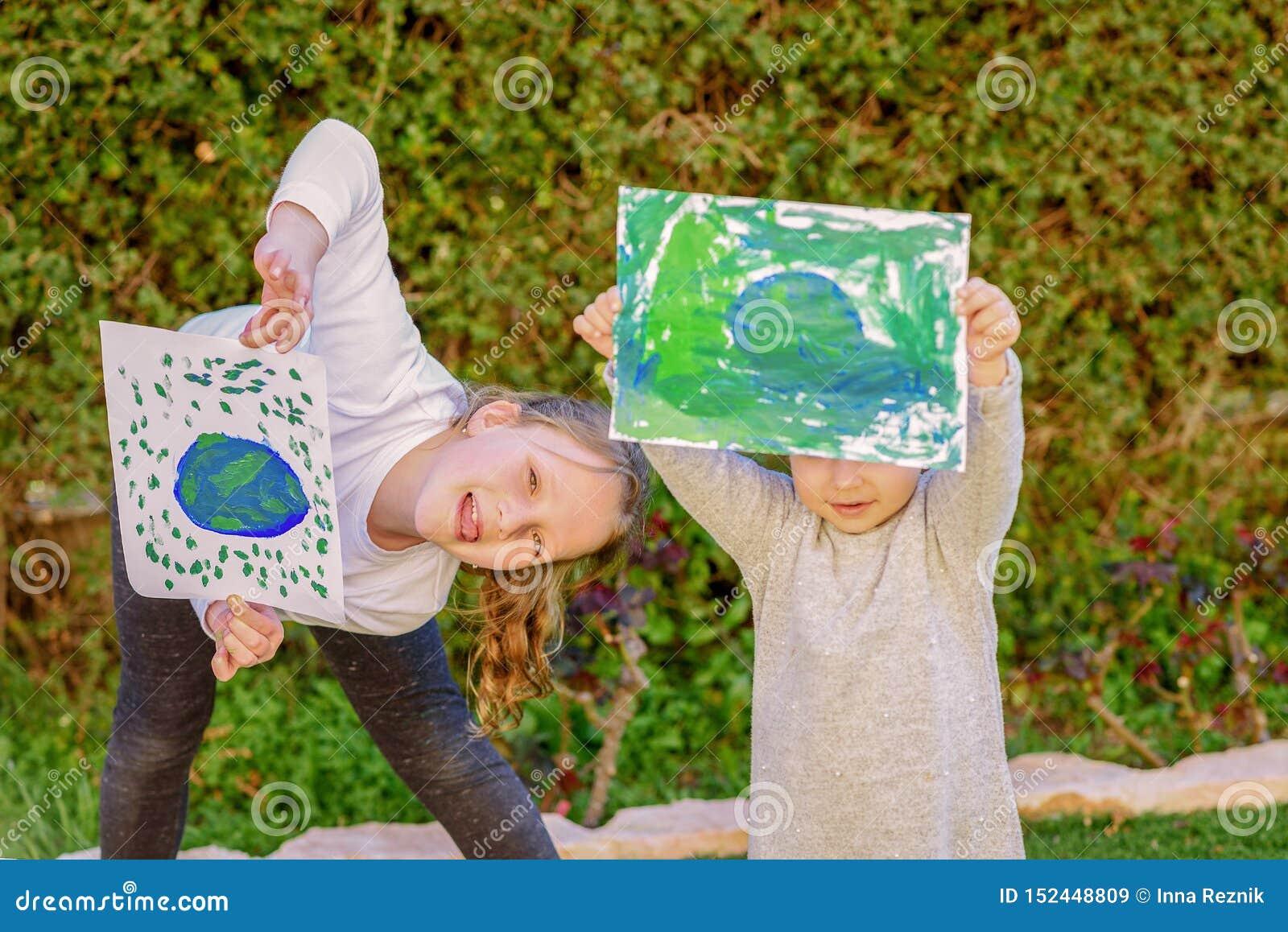 Stående av de två gulliga små flickorna som rymmer det dra jordjordklotet Ungepaintigbild av jord som har roligt utomhus-