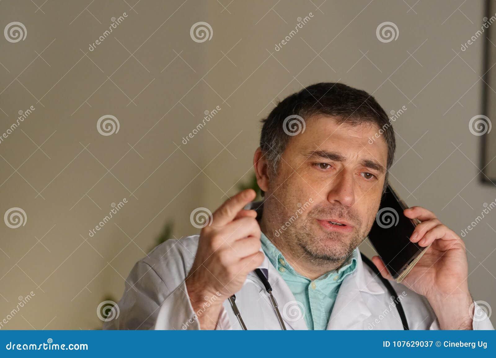 Stående av den absorberade doktorn som talar på hans mobiltelefon