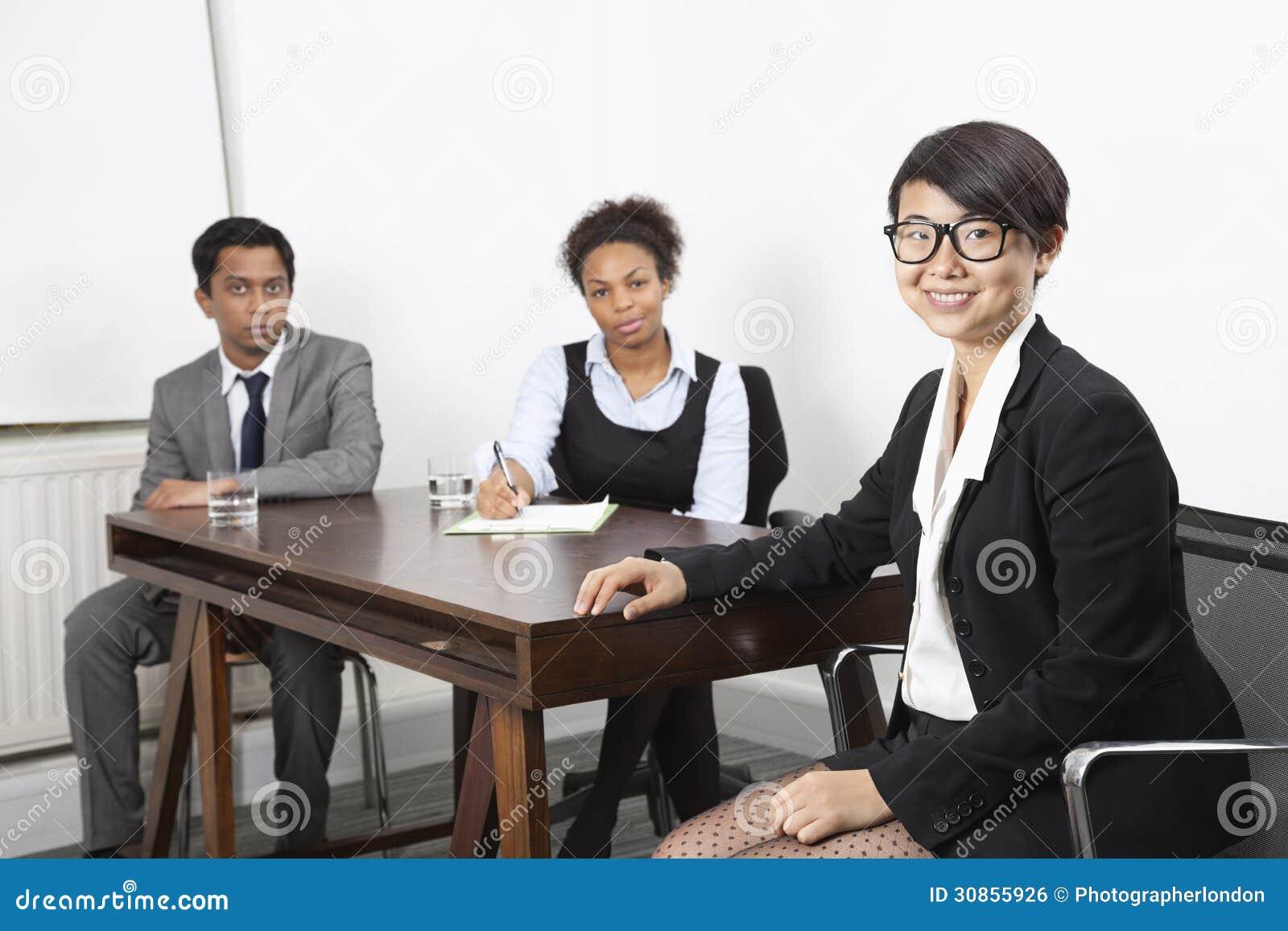 Stående av den asiatiska kvinnlign med multietniska kollegor i bakgrund på skrivbordet i regeringsställning
