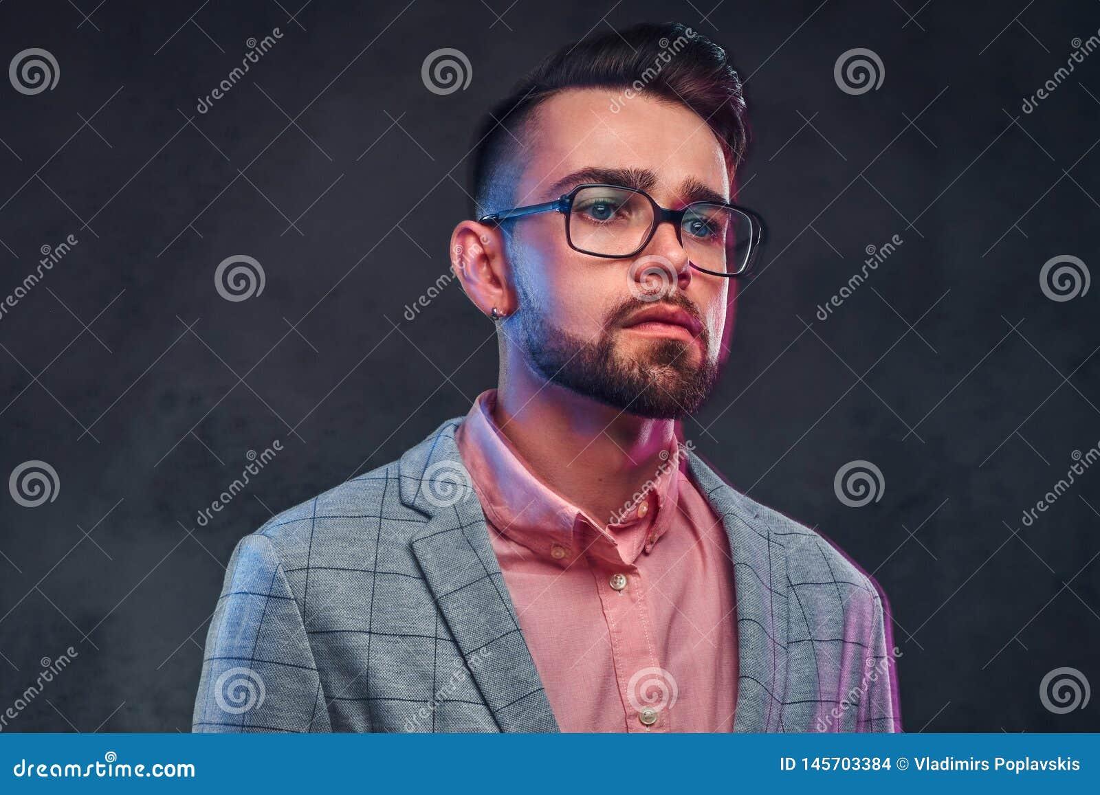 Stående av den attraktiva eftertänksamma mannen i rutig blazer, rosa skjorta och exponeringsglas