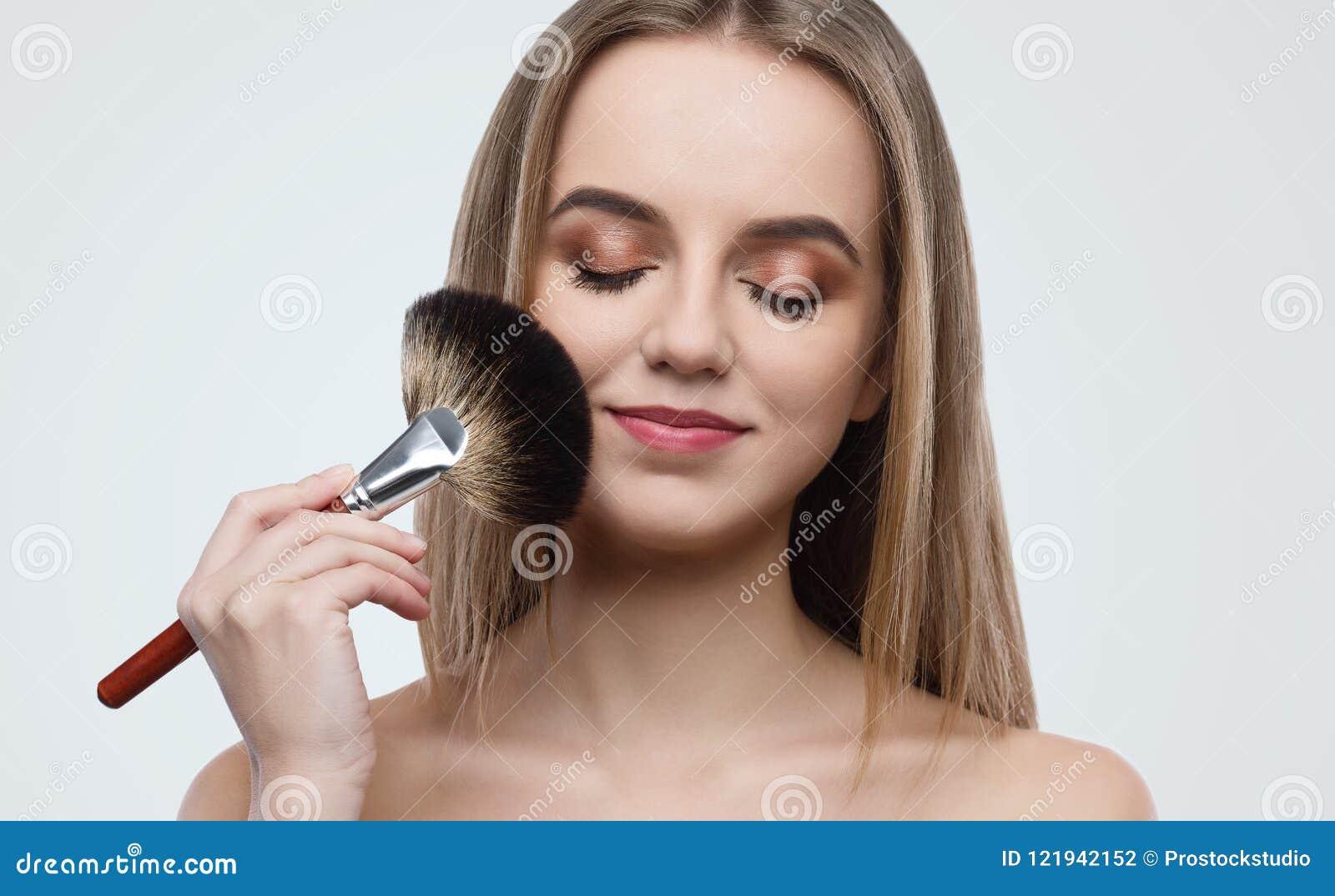 Stående av den attraktiva innehavborsten för ung kvinna