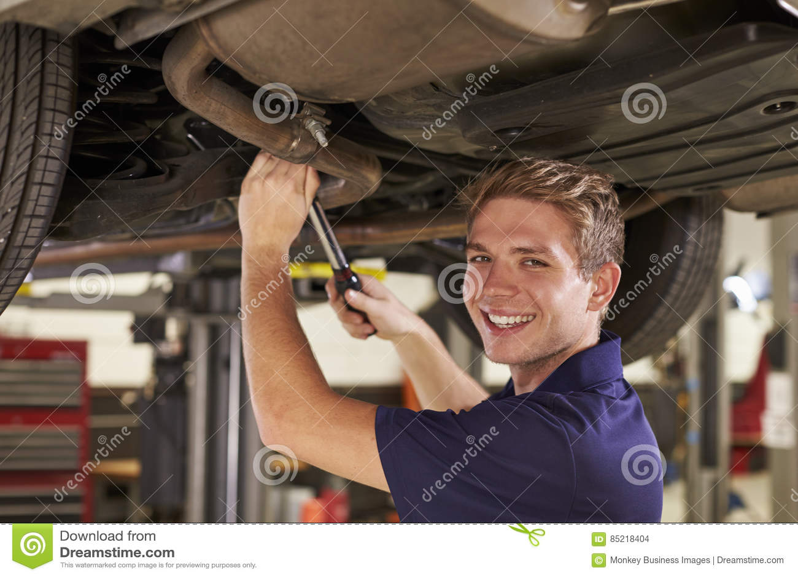 Stående av den auto mekanikern Working Underneath Car i garage