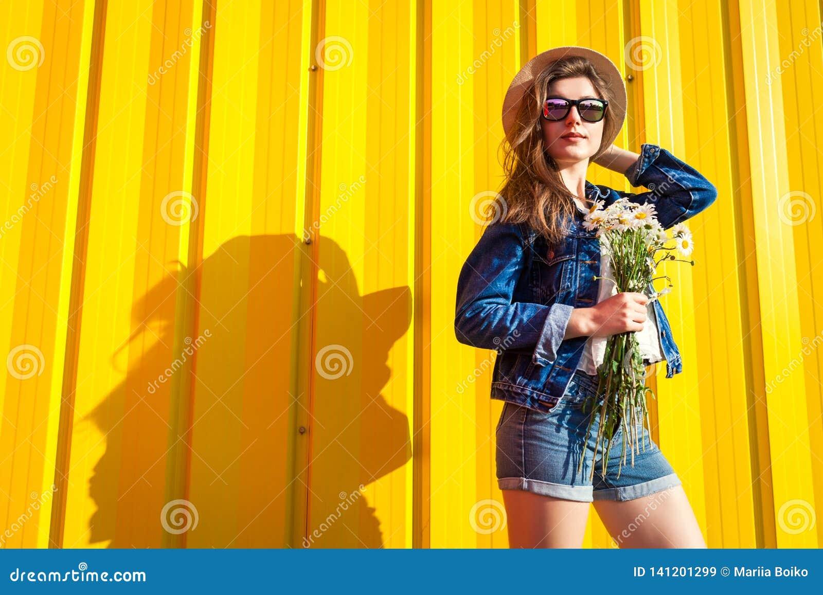 Stående av den bärande exponeringsglas och hatten för hipsterflicka med blommor mot gul bakgrund Sommardräkt Mode avstånd