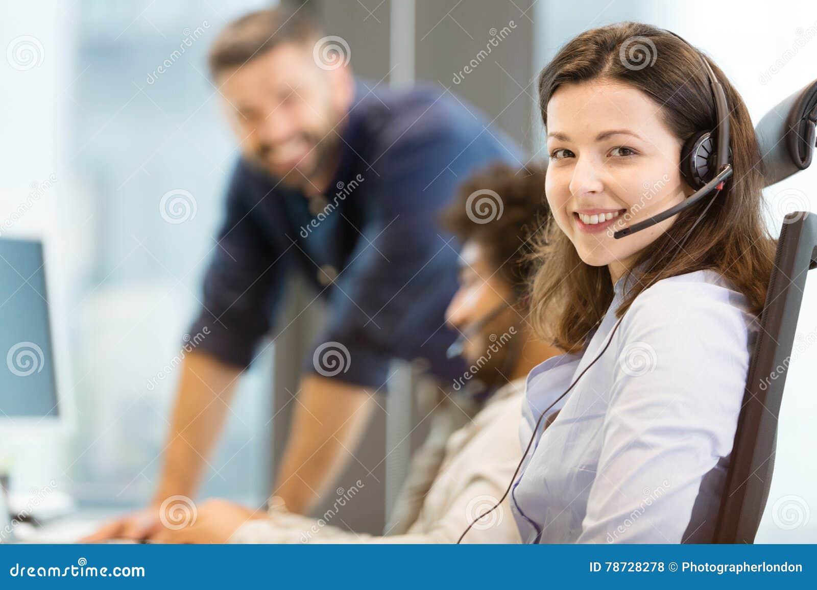 Stående av den bärande hörlurar med mikrofon för ung affärskvinna med kollegor i bakgrund på kontoret