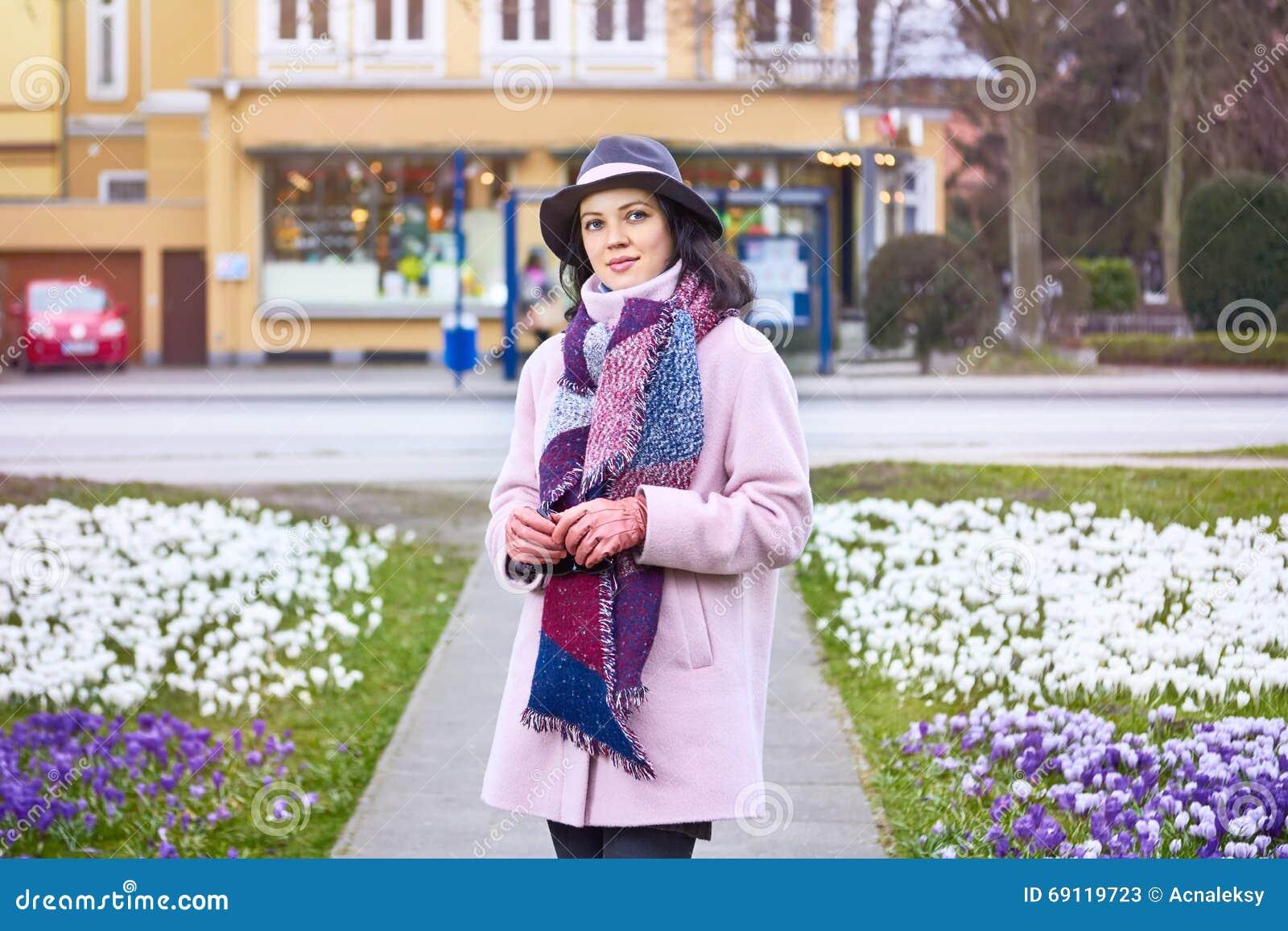 Stående av den bärande hatten för ung härlig kvinna som går i spren
