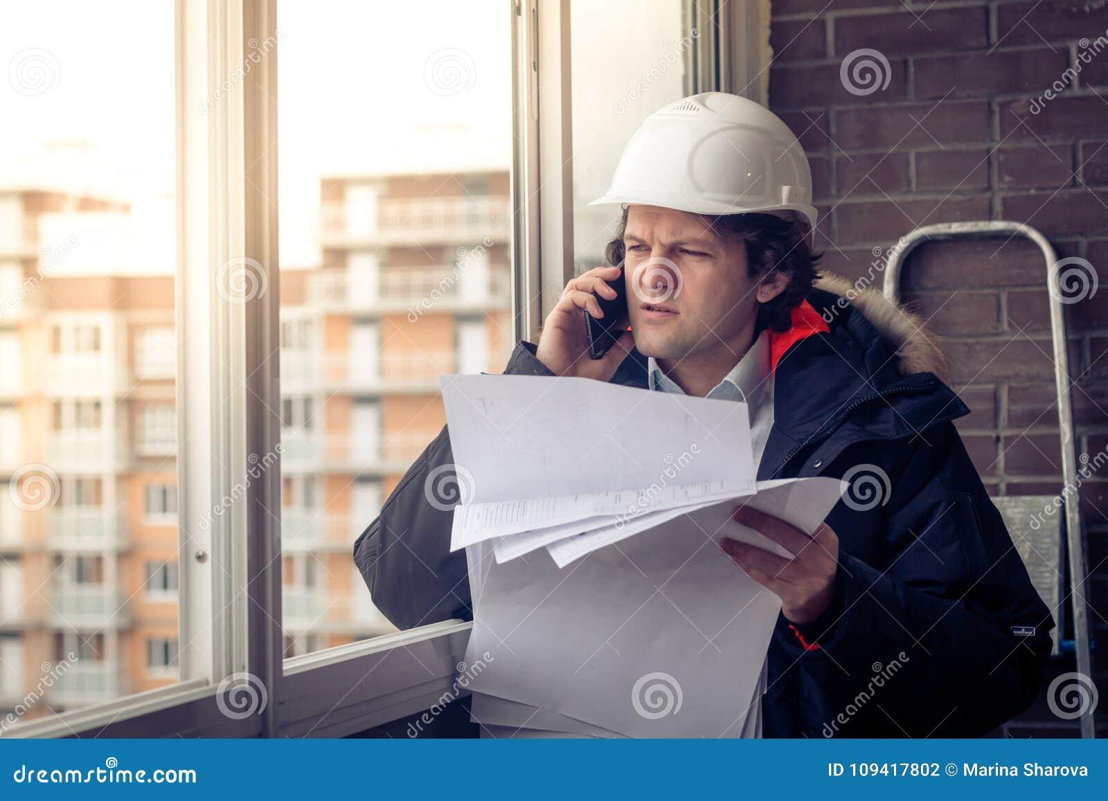 Stående av den bekymrade orakade byggmästaren som berättar vid mobilen, medan hålla olika projekt i hand Kommunikation och