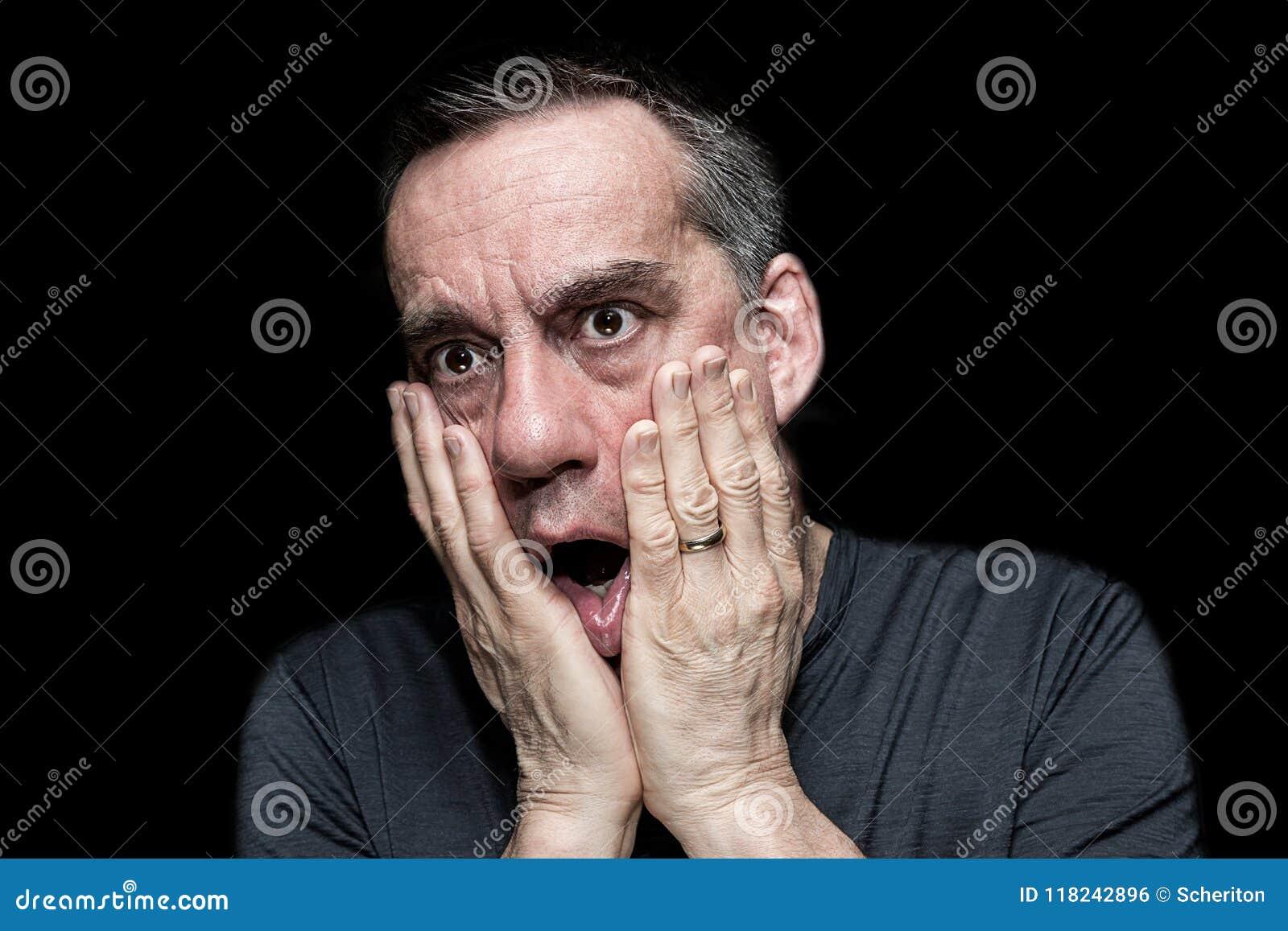 Stående av den chockade förfärade mannen med händer som ska vändas mot