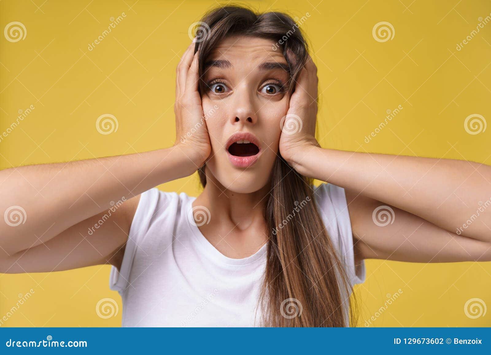 Stående av den chockade förskräckta unga kvinnan i tillfällig vit skjortautfrågningdåliga nyheter med äcklig sinnesrörelse på hen