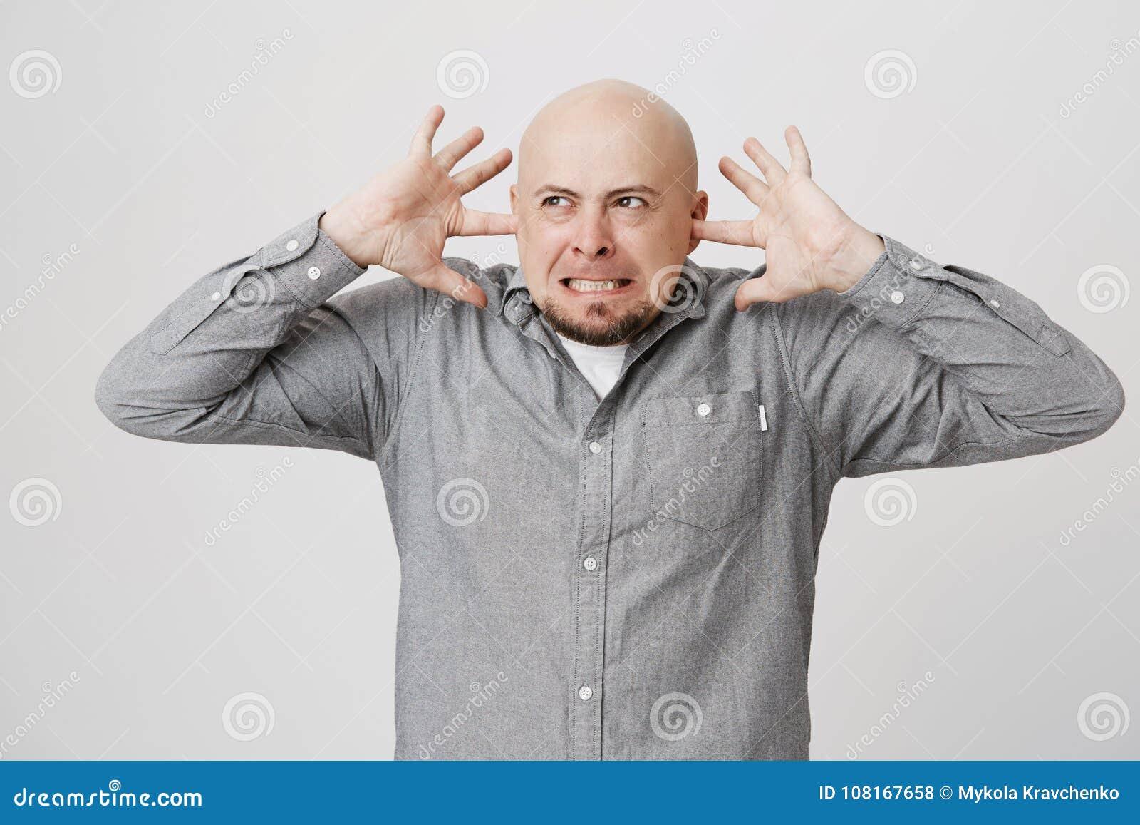 Stående av den förargade och ilskna grabben med skägget som stänger hans öron med fingrar över vit bakgrund Man i ett dåligt lynn