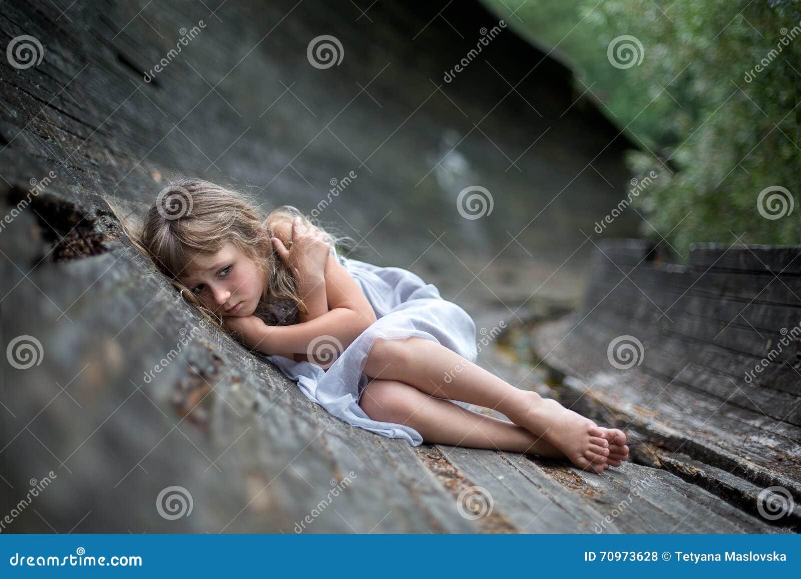 Stående av den förskräckta lilla flickan i skog