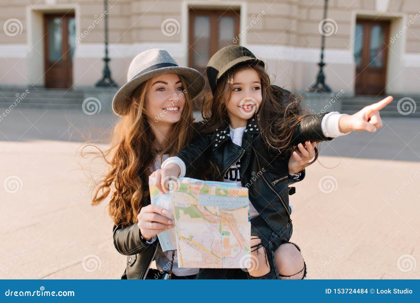 Stående av den förtjusande lilla flickan i moderiktig hatt som pekar med fingret på sikt i ny stad under lopp med mamman