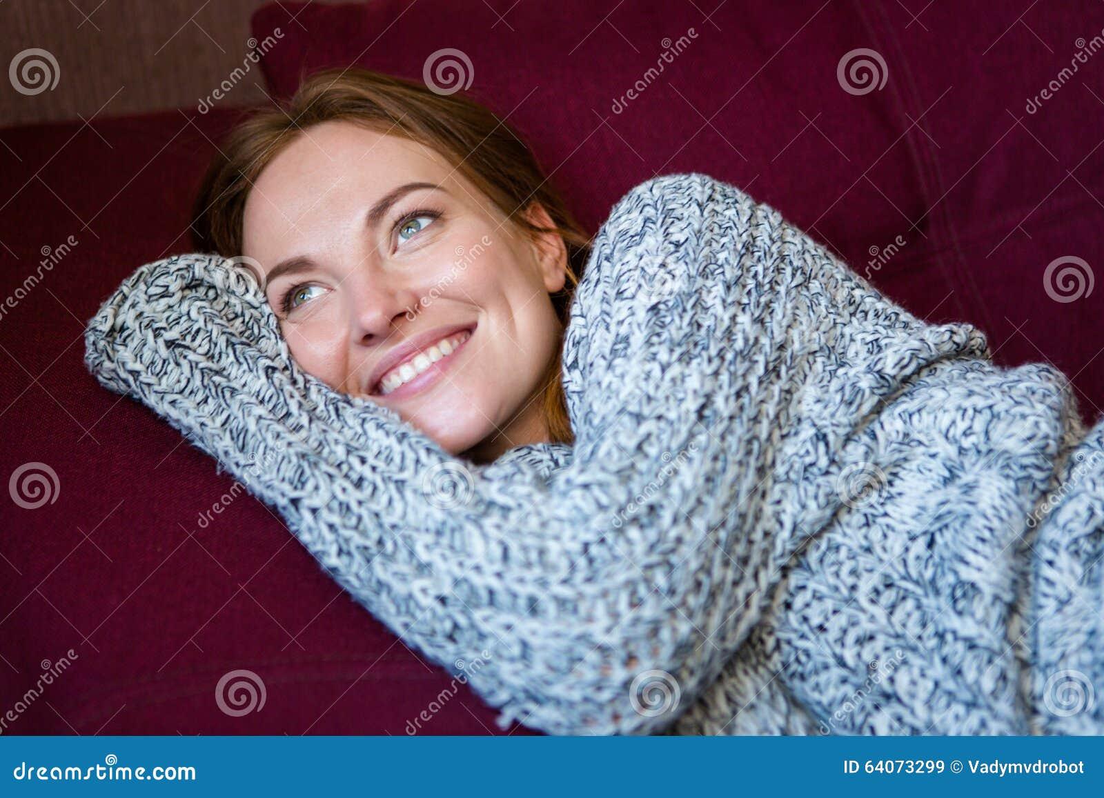 Stående av den gladlynta kvinnan i den stack tröjan som ligger på soffan