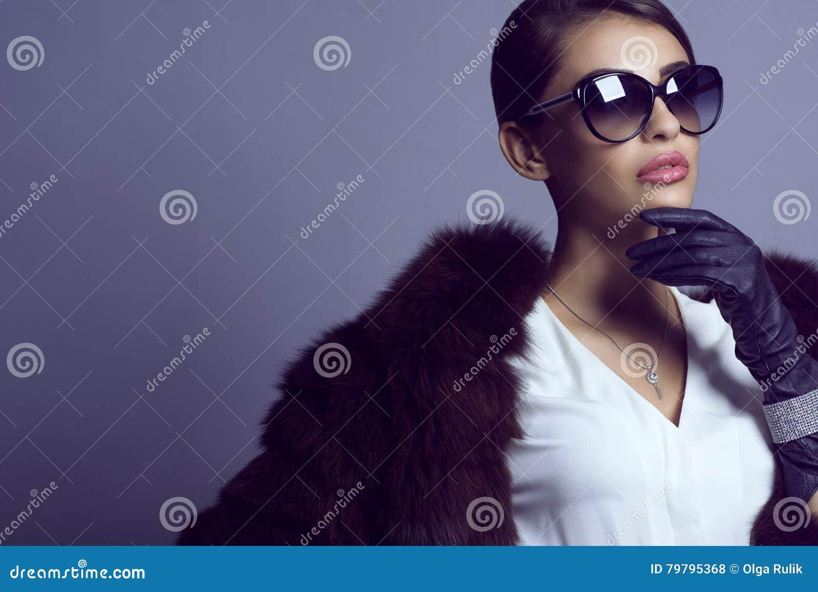 Stående av den glam mörker-haired modellen i stilfull klassisk solglasögon som bär den vita blusen, det svarta laget och uppsättn