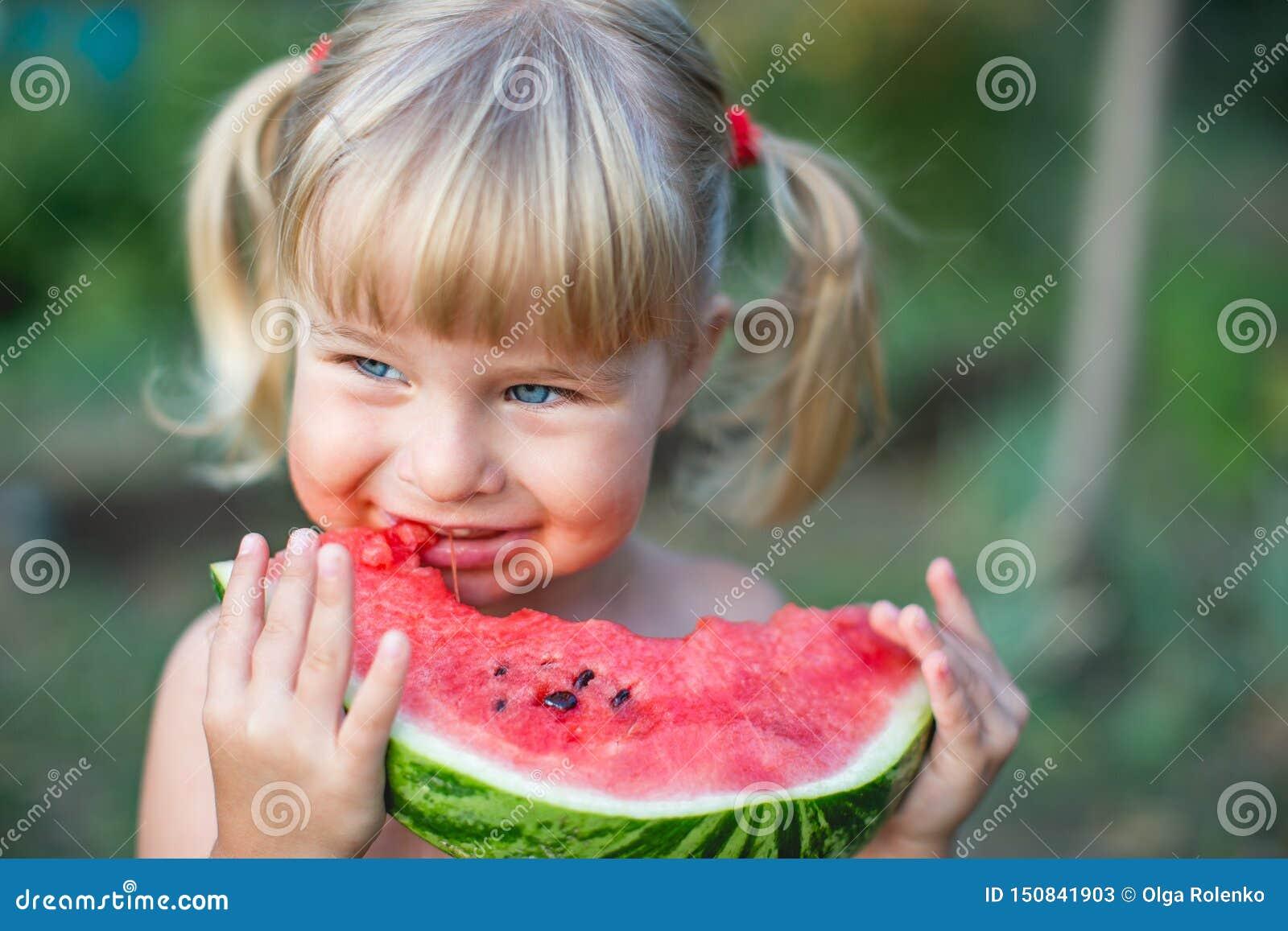 Stående av den härliga blonda lilla flickan med två hästsvansar som äter vattenmelon