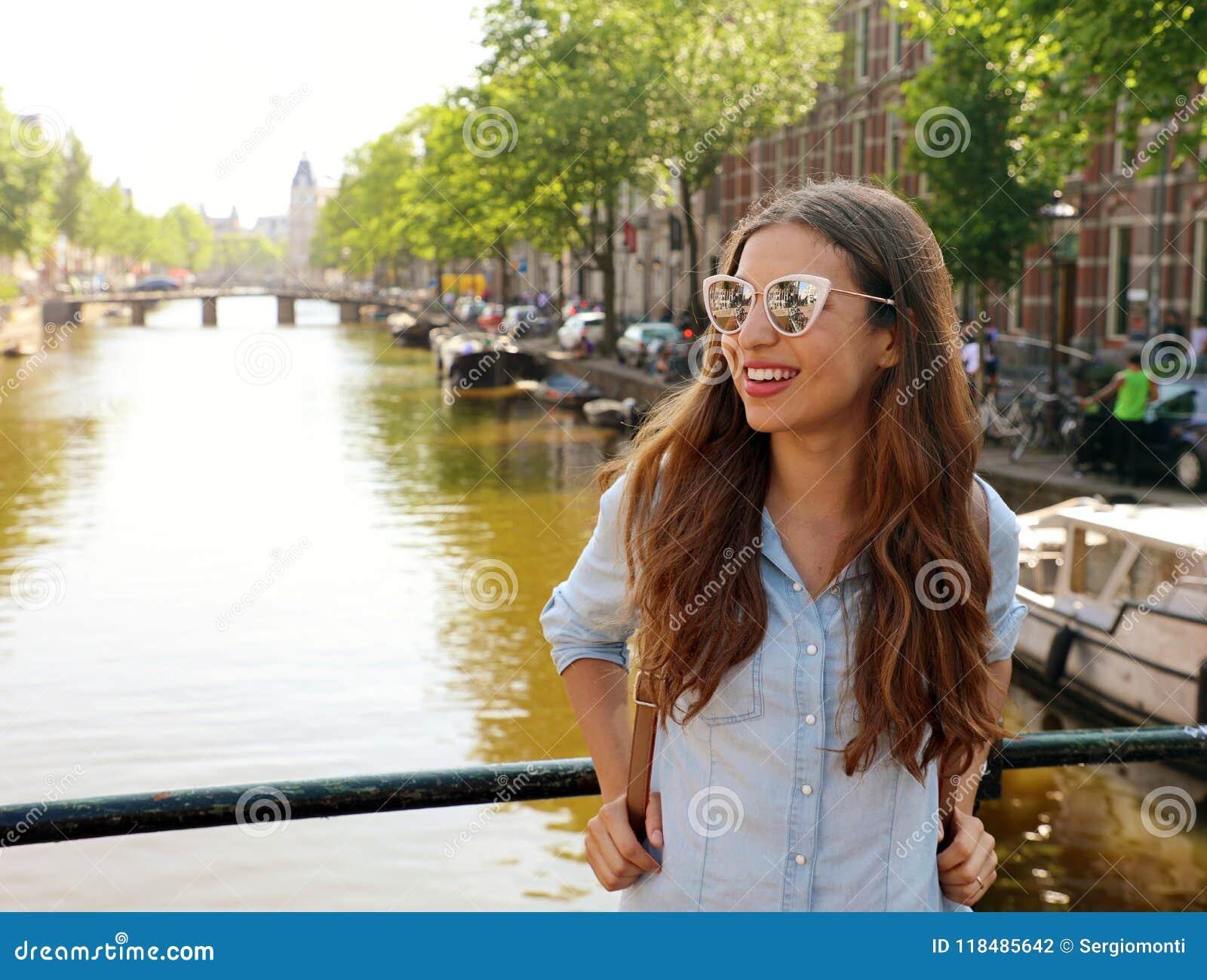 Stående av den härliga gladlynta flickan med solglasögon som ser till sidan på en av typiska Amsterdam kanaler, Nederländerna