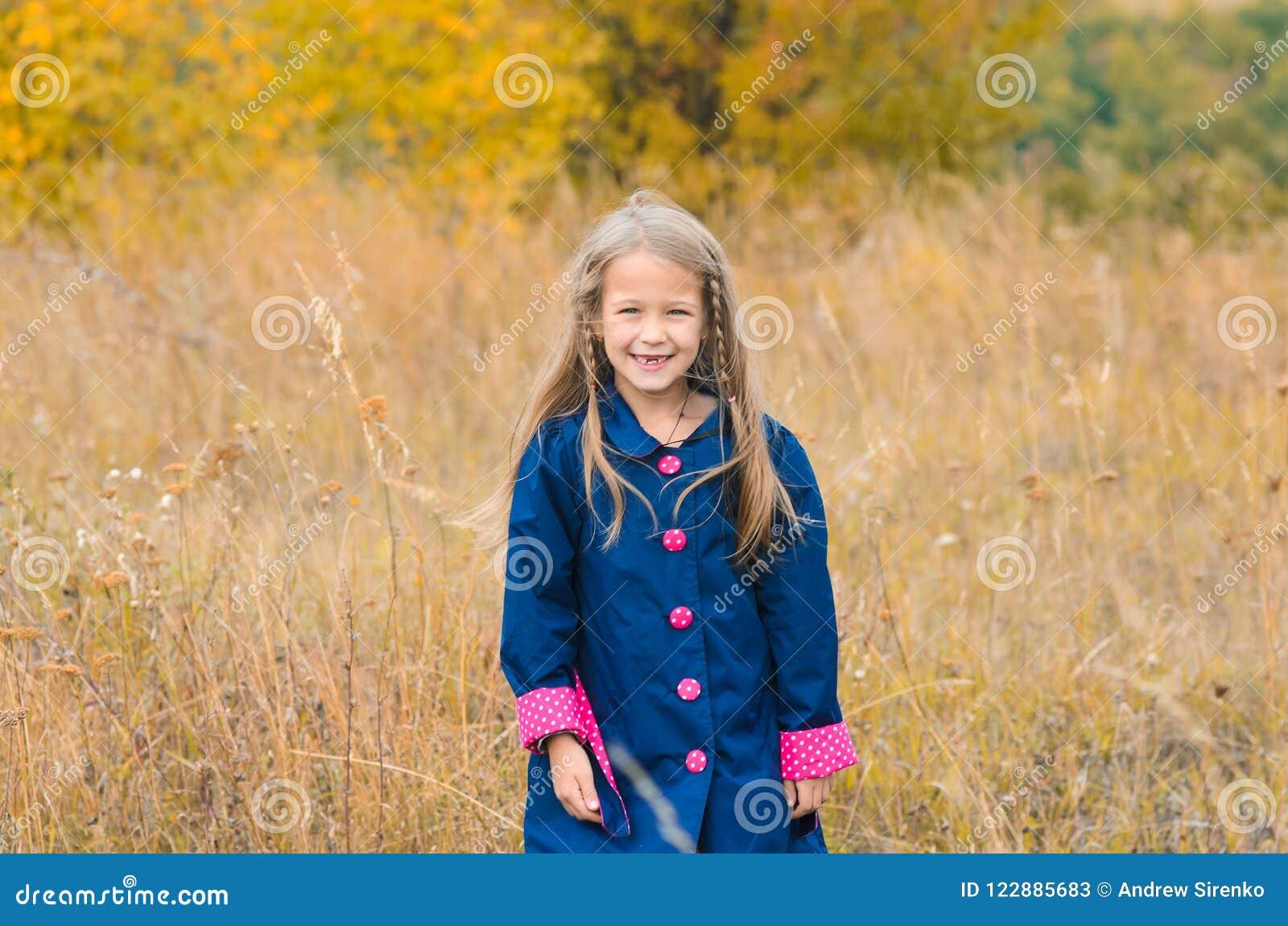 Stående av den härliga gulliga flickan i kläder på bakgrund av autuen