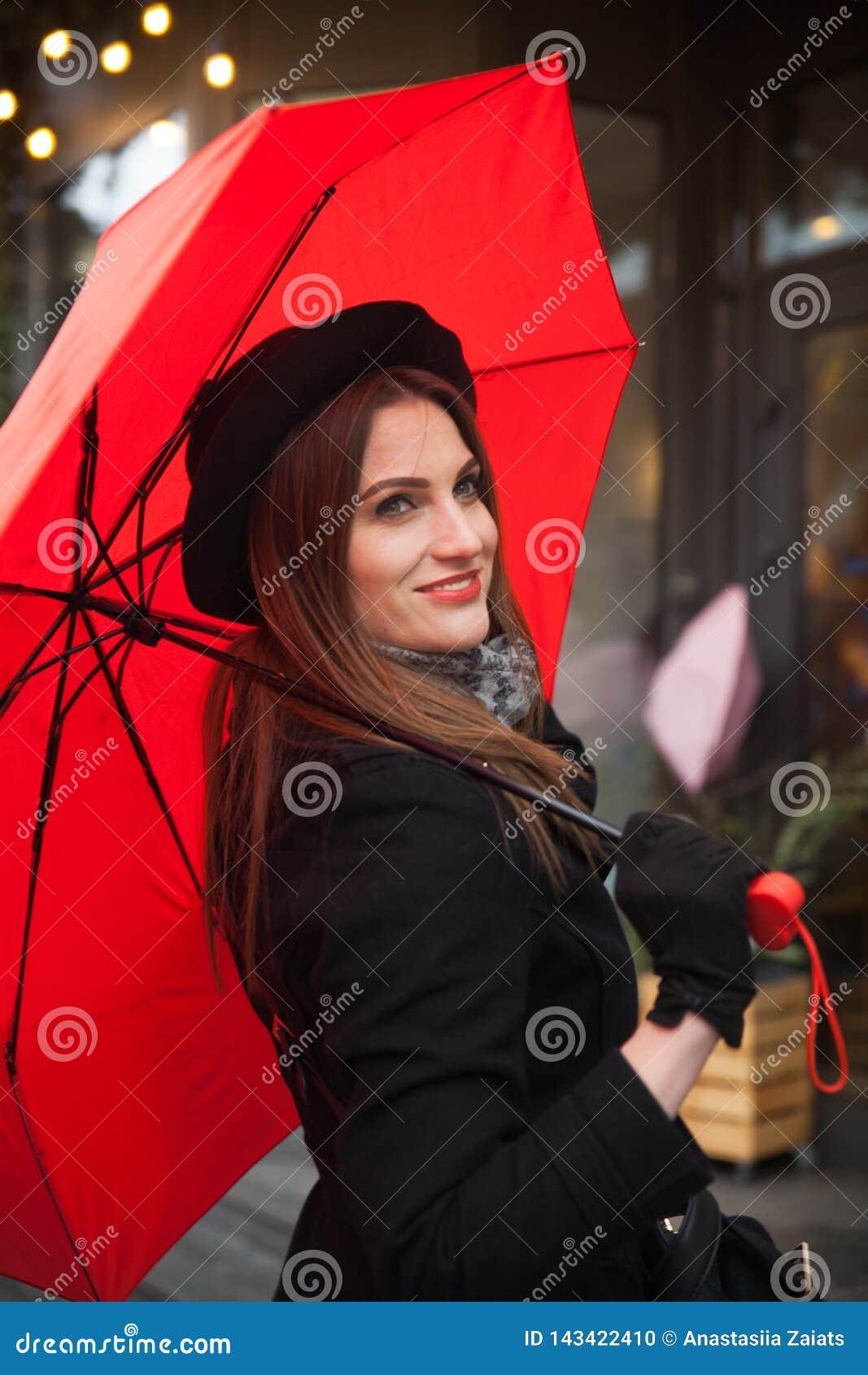 Stående av den härliga kvinnan med det röda paraplyet framme av ett kafé i staden
