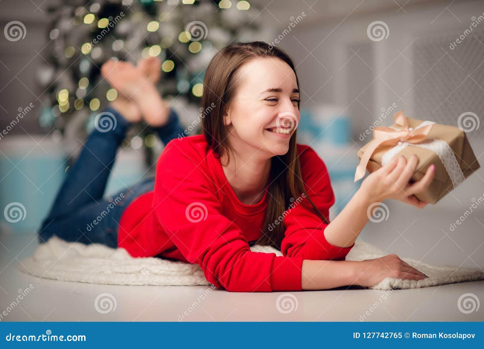 Stående av den härliga kvinnan med gåvasammanträde vid julgranen hemma