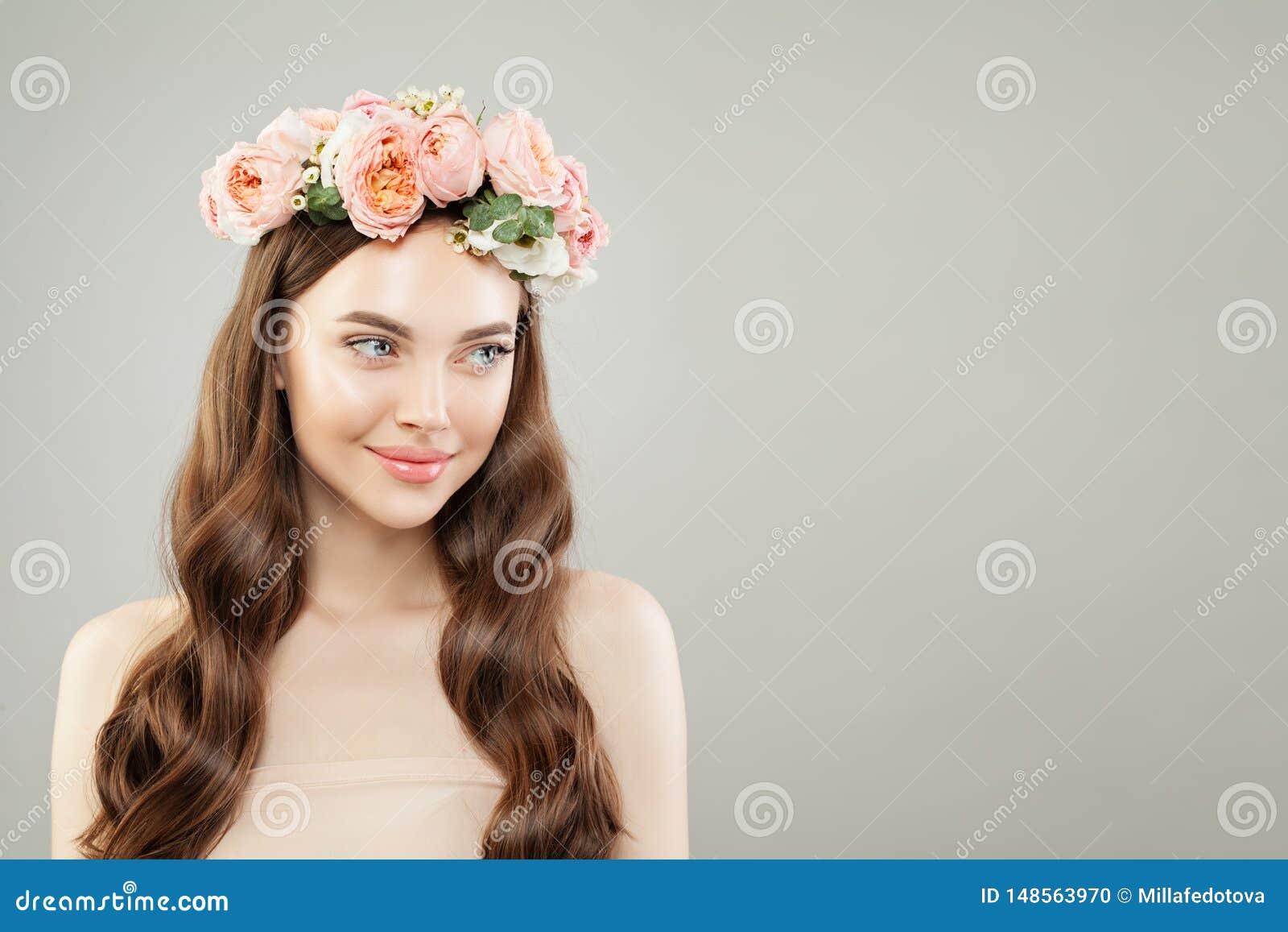 Stående av den härliga le kvinnan med klar hud, långt skinande hår och blommor Skincare och ansikts- behandlingbegrepp