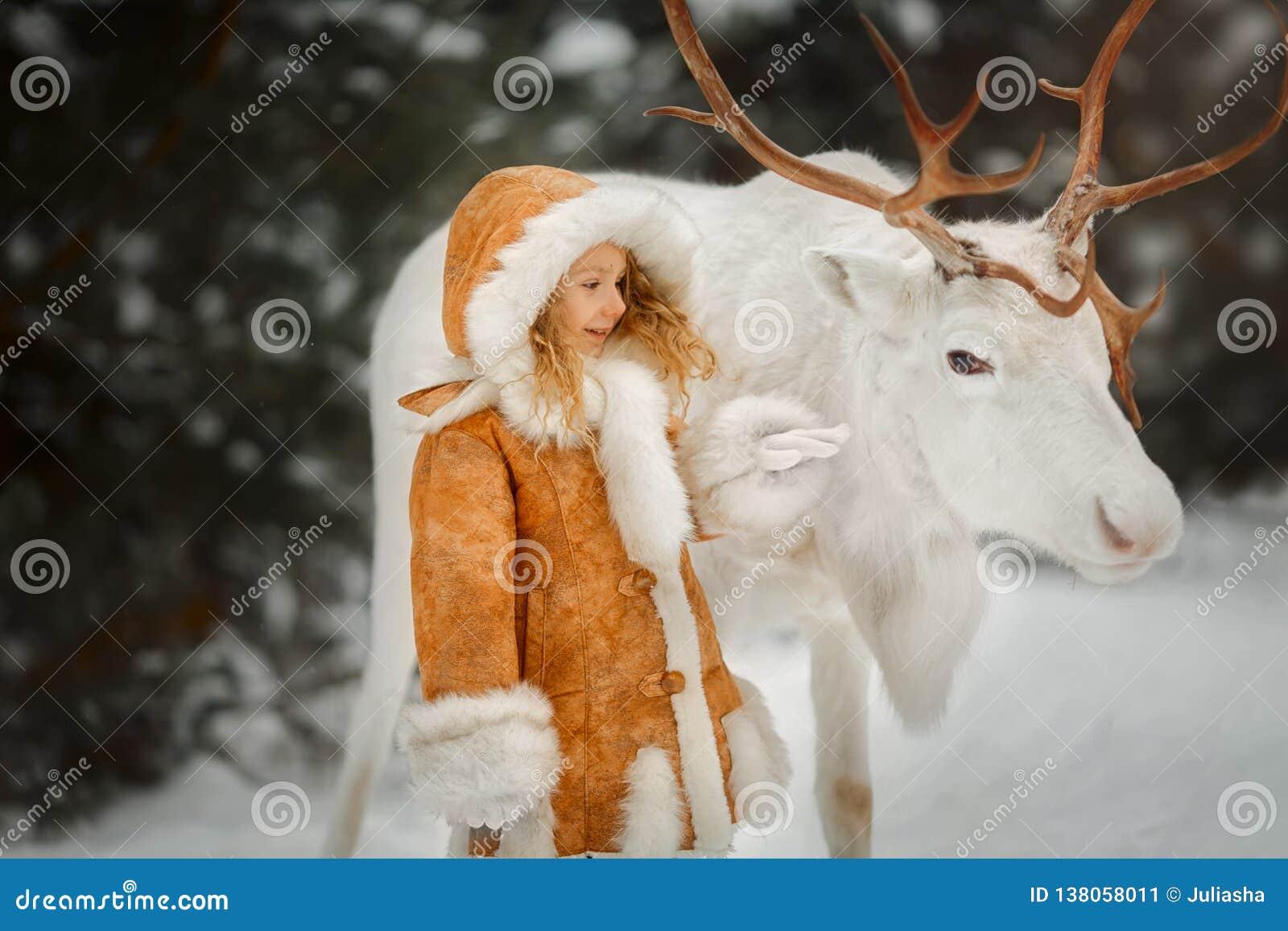 Stående av den härliga lilla flickan i pälslag på vinterskogen