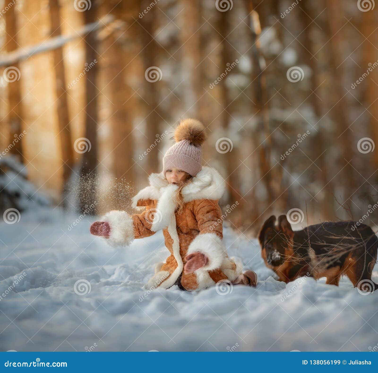 Stående av den härliga lilla flickan och valpen på vinterskogen