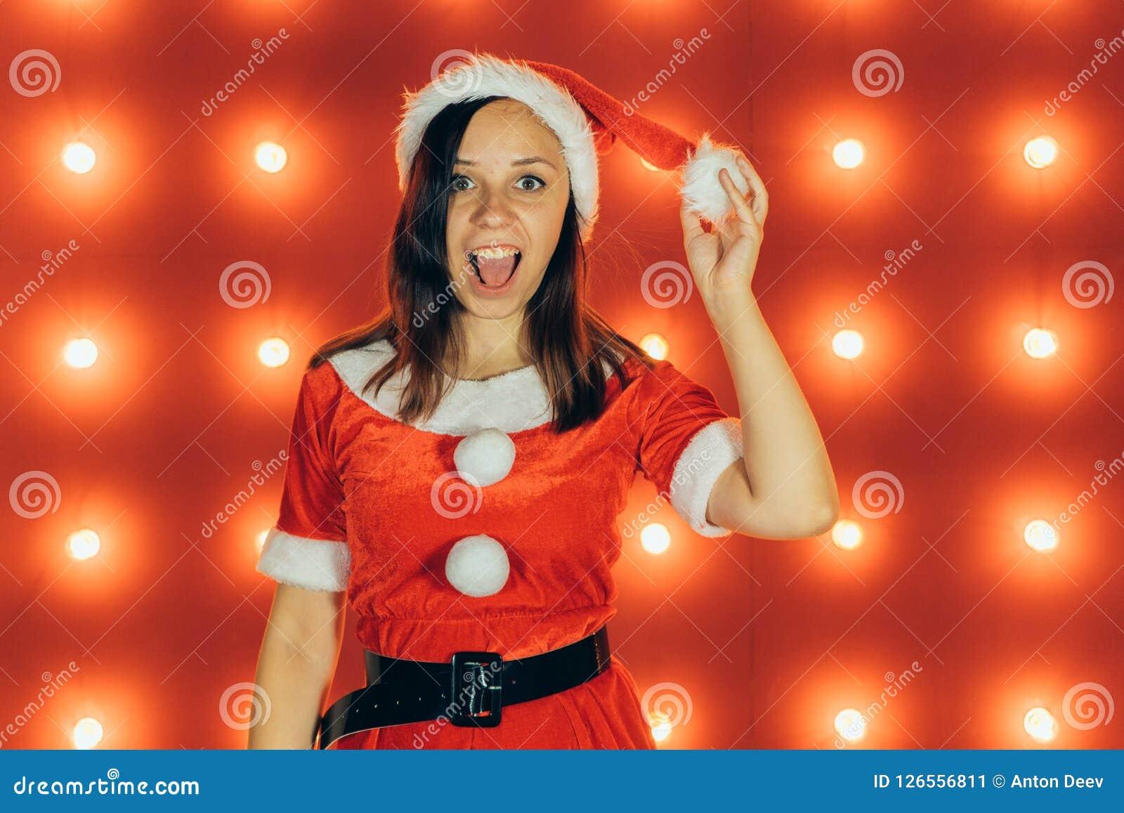 Stående av den härliga sexiga flickan som bär Santa Claus kläder på röd bakgrund