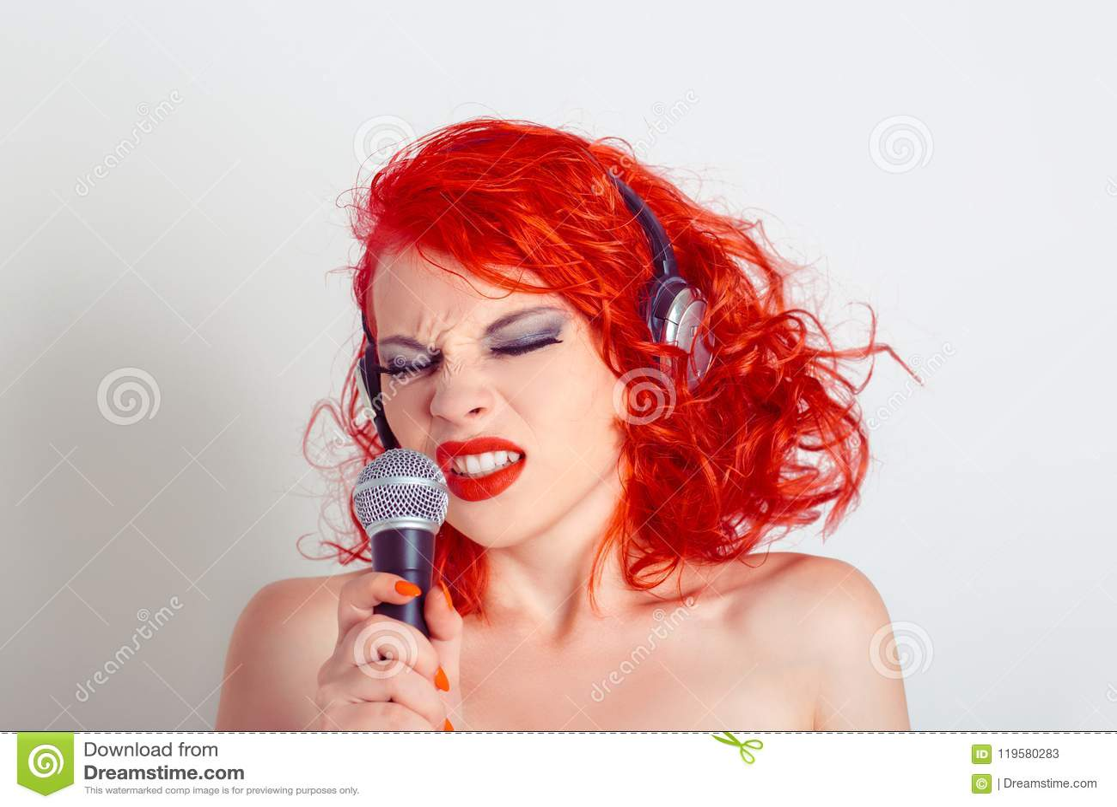 Stående av den härliga unga kvinnan i hörlurar som sjunger in i en mikrofon