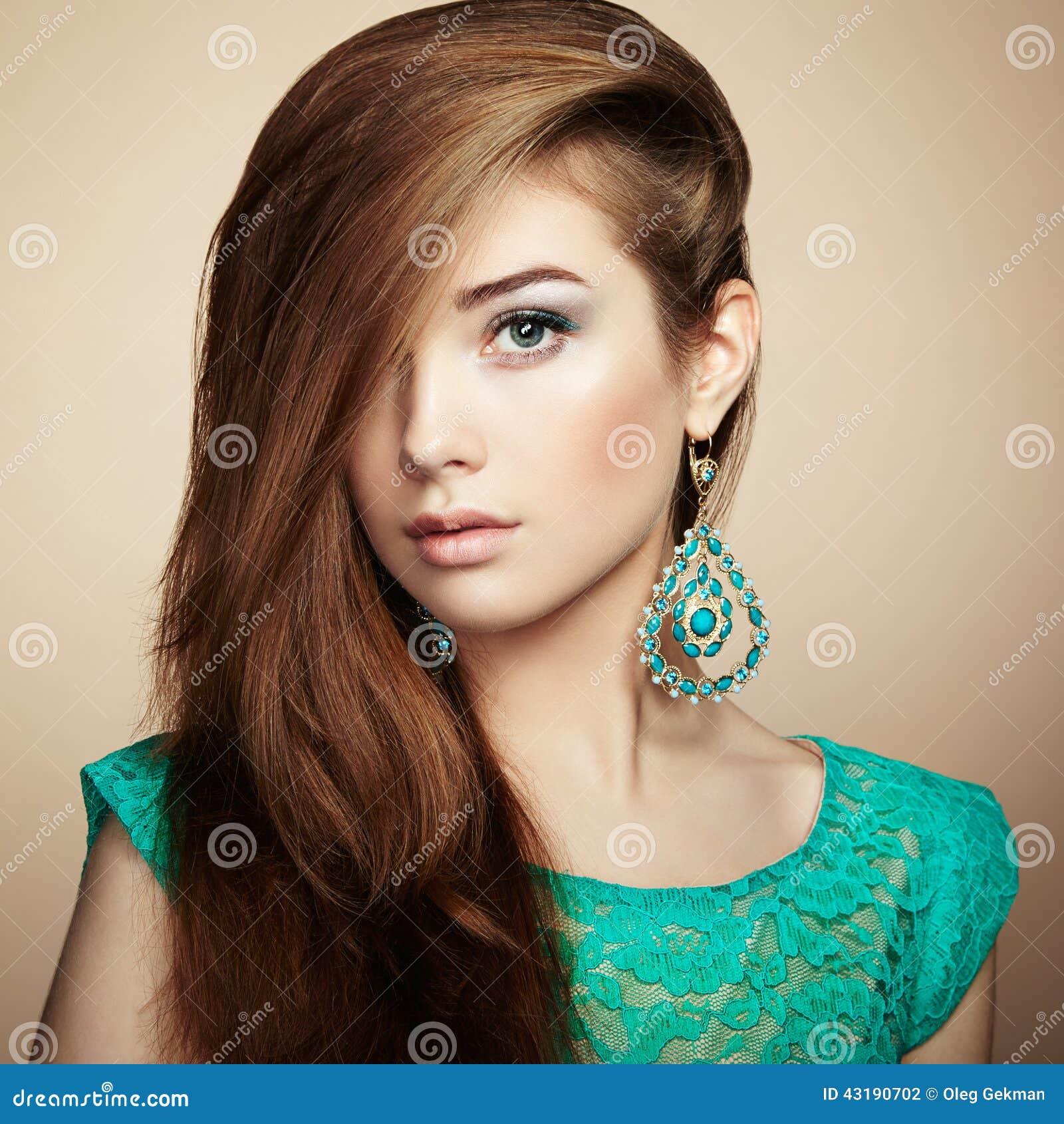 Stående av den härliga unga kvinnan med örhänget Smycken och acce