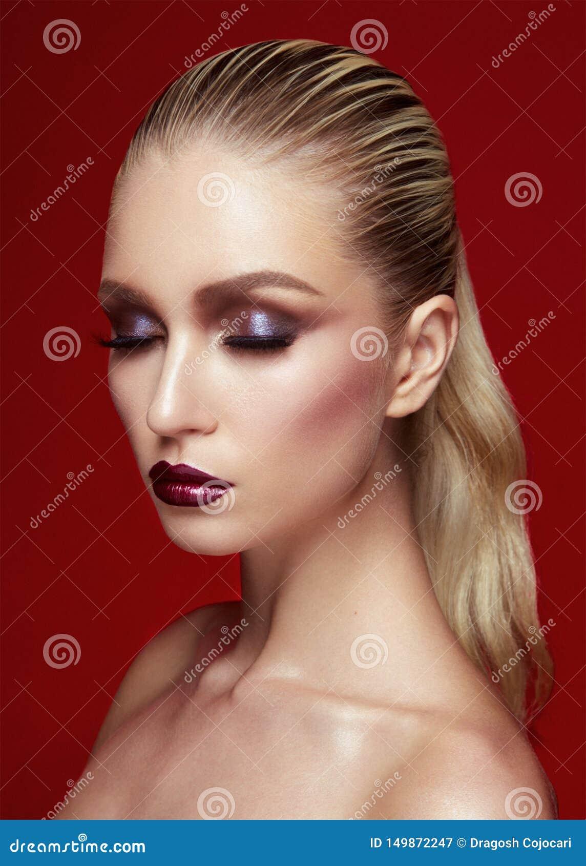 Stående av den härliga unga kvinnan med perfekt makeup Stängda ögon modellerar, med hår som rätas ut på burgundy bakgrund