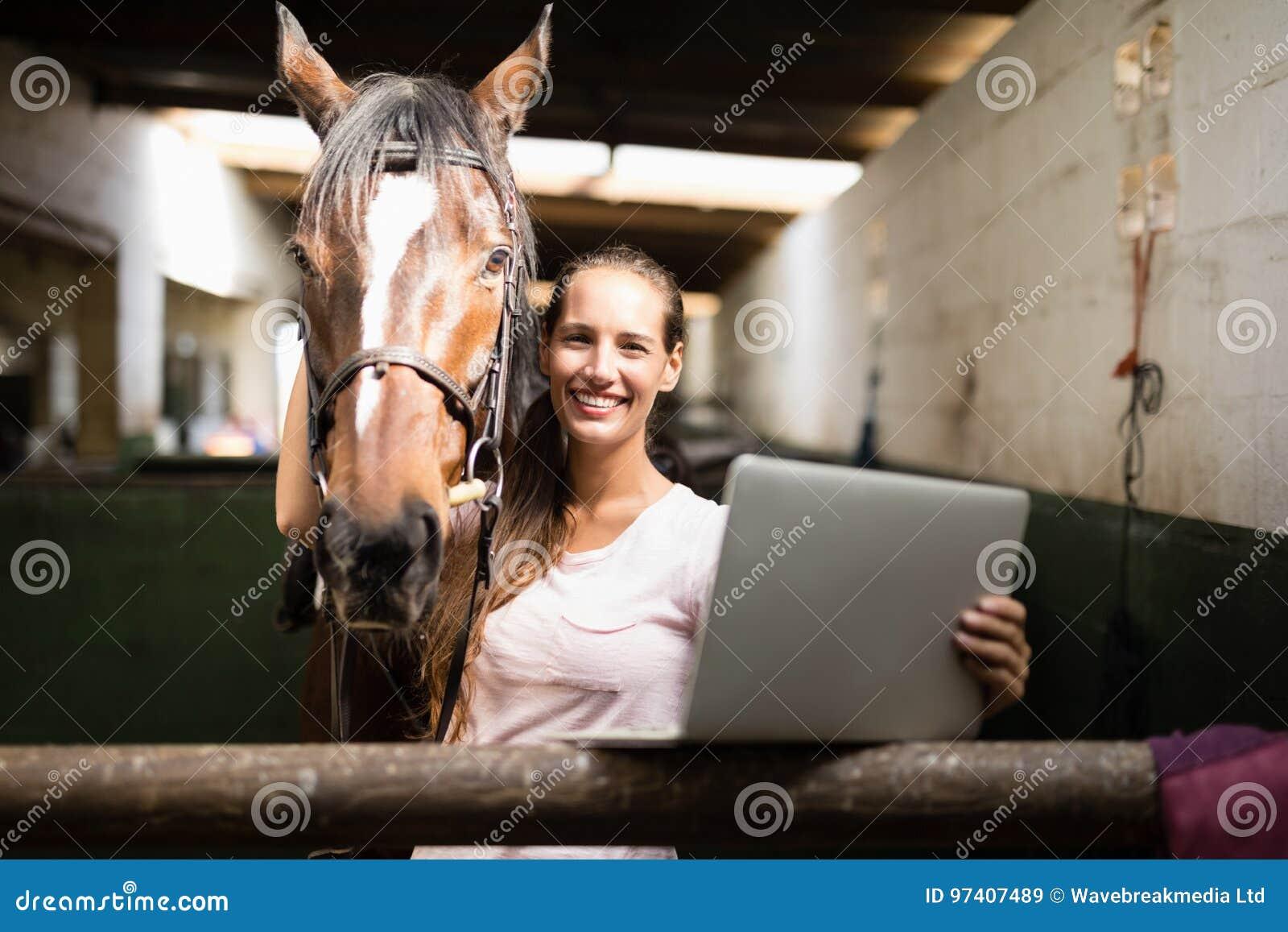 Stående av den hållande bärbara datorn för kvinnlig jockey, medan stå vid hästen