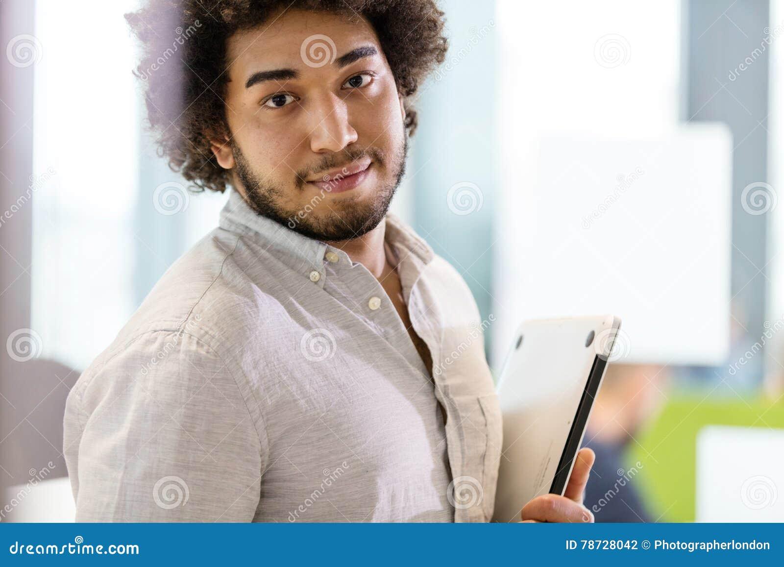 Stående av den hållande bärbara datorn för säker ung affärsman på kontoret
