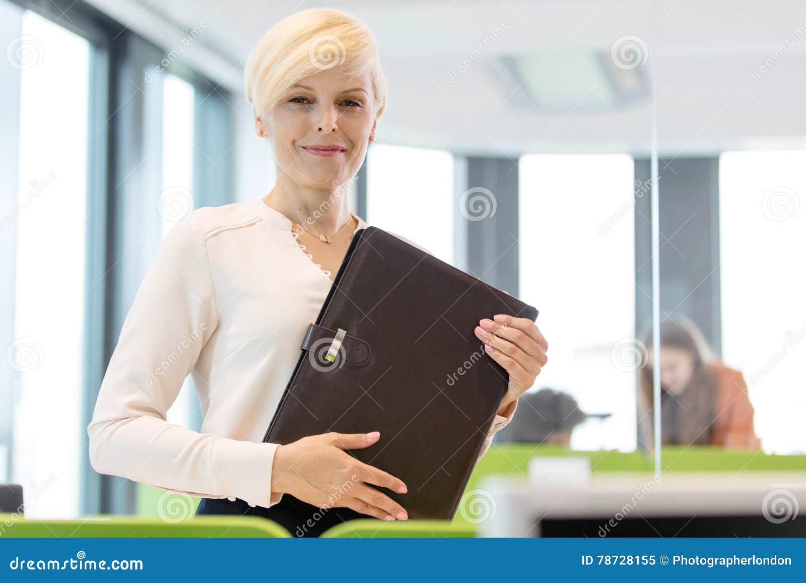 Stående av den hållande mappen för mogen affärskvinna i regeringsställning