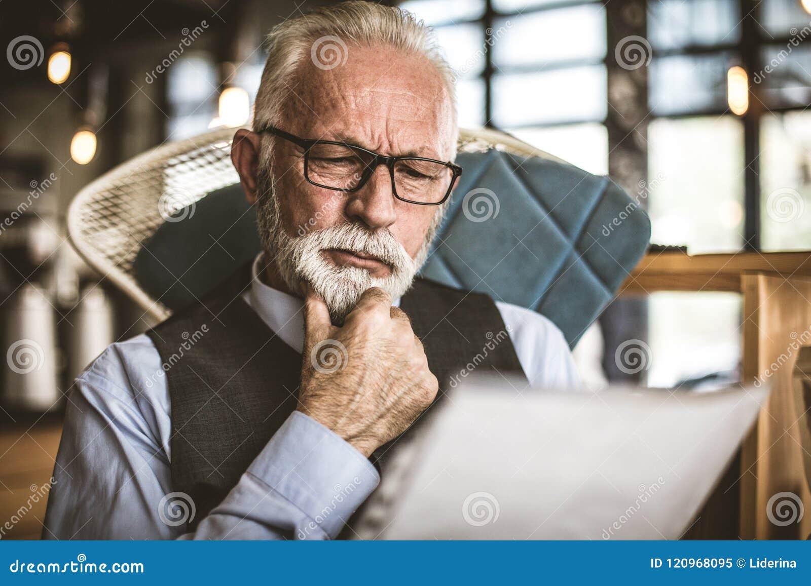 Stående av den höga affärsmannen som ser dokument close upp