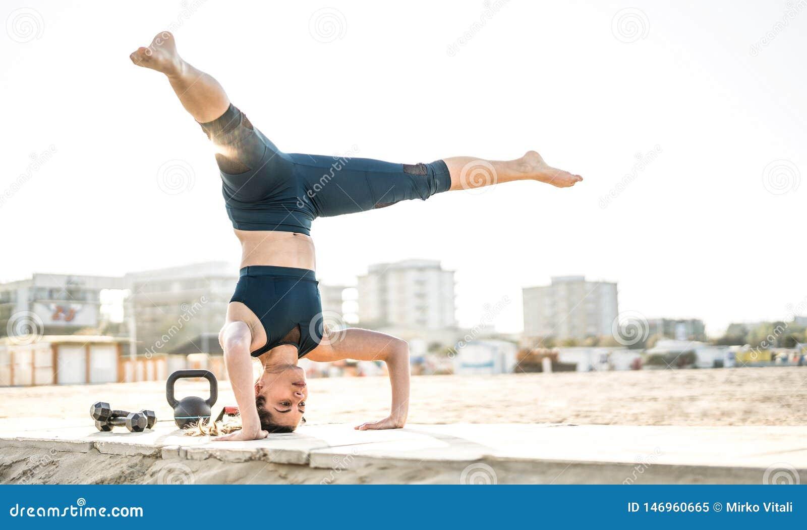 Stående av den idrotts- kvinnan som övar calisthenic jämviktsflyttning på det friastrandläge - modernt alternativ att utarbeta