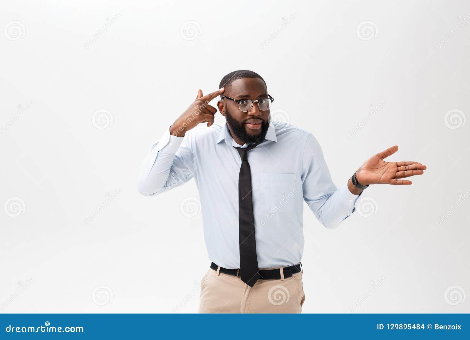Stående av den ilskna eller förargade unga afrikansk amerikanmannen i den vita poloskjortan som ser kameran med misshagit