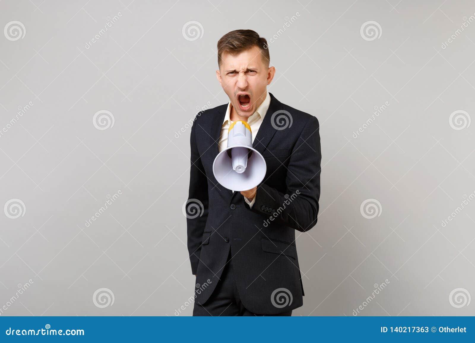Stående av den ilskna unga affärsmannen i klassisk svart dräkt och skjortan som skriker på megafonen som isoleras på den gråa väg