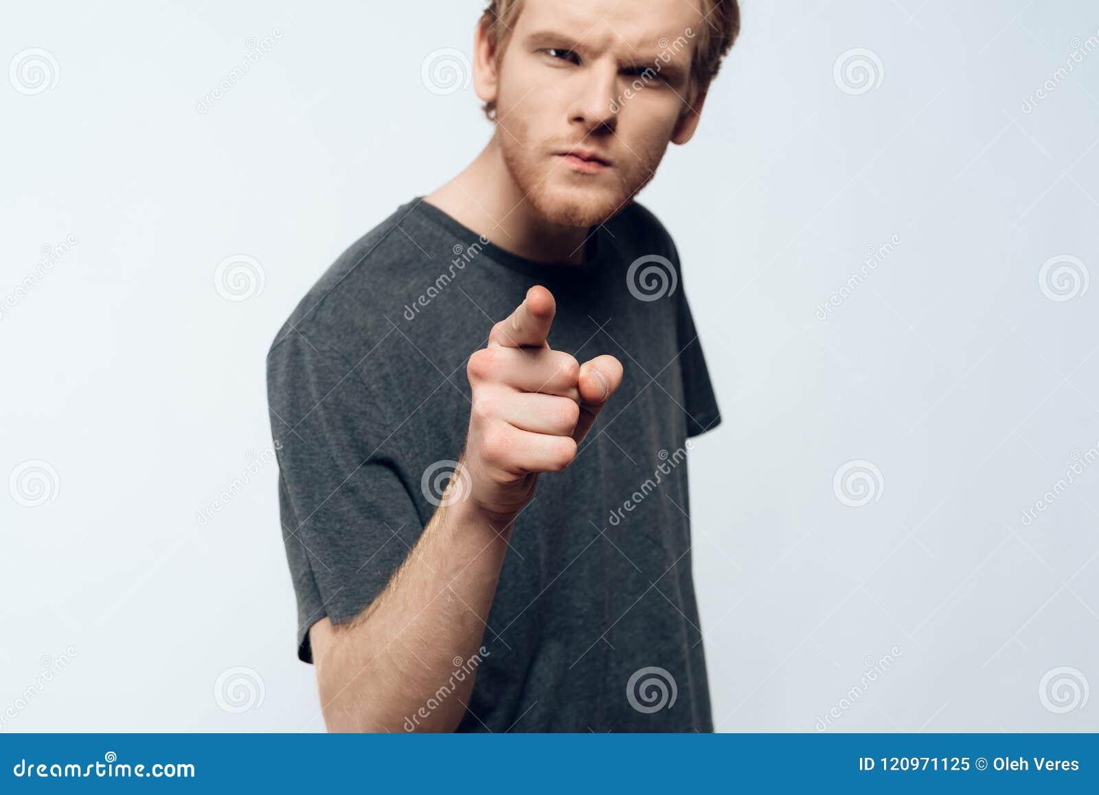 Stående av den ilskna unga mannen som pekar pekfingret