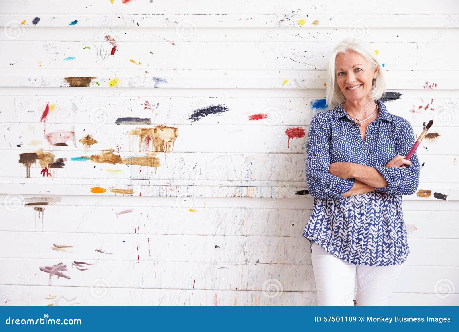 Stående av den kvinnliga konstnärAgainst Paint Covered väggen