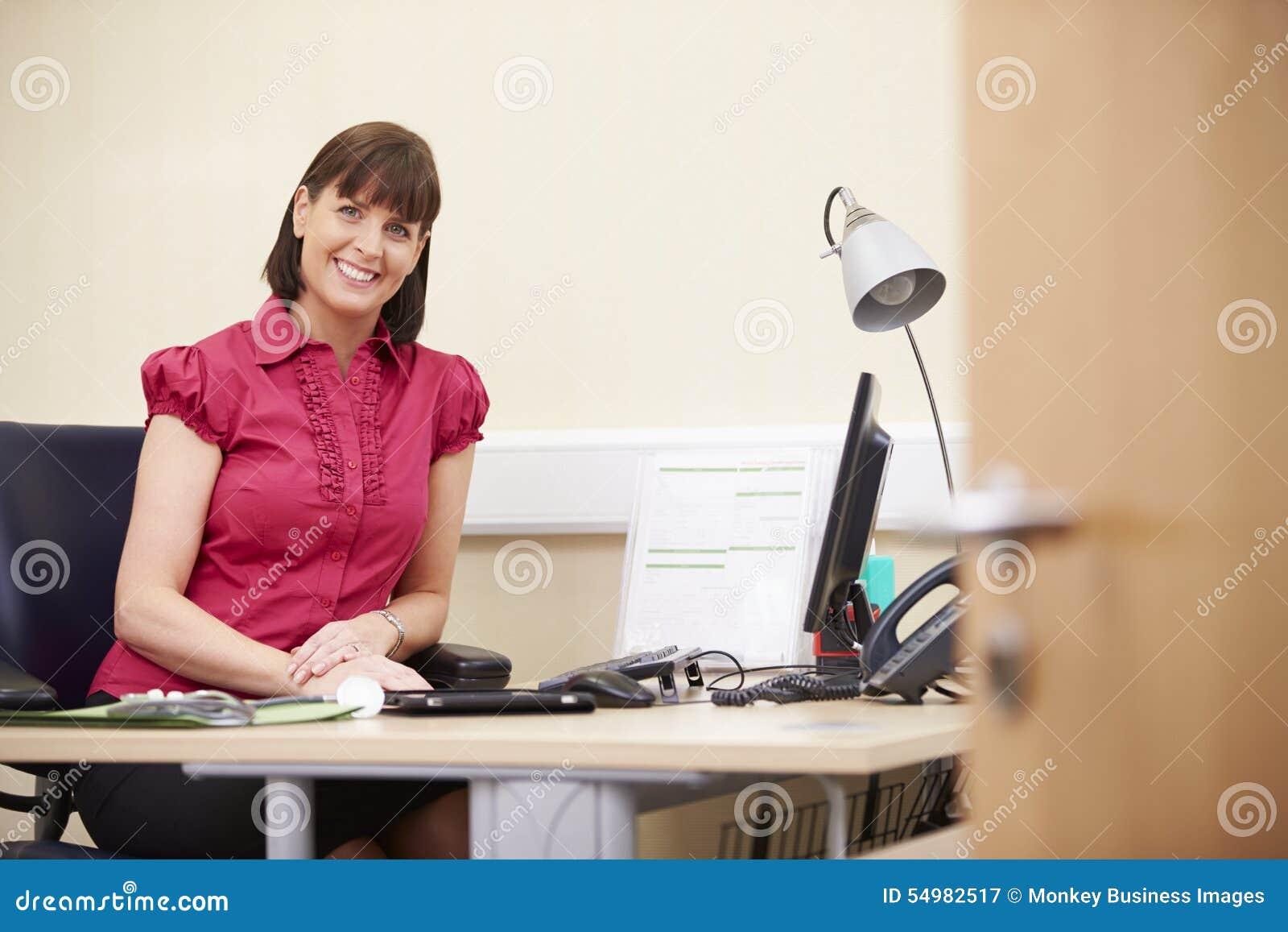 Stående av den kvinnliga konsulenten Working At Desk i regeringsställning