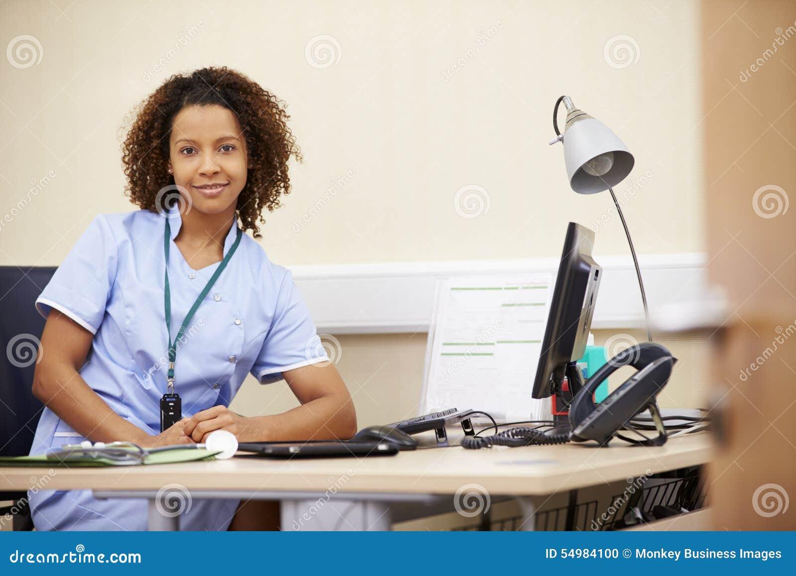 Stående av den kvinnliga sjuksköterskan Working At Desk i regeringsställning