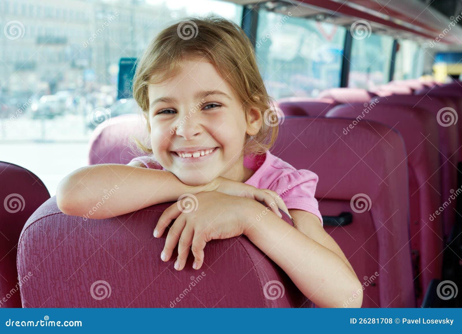 Stående av den le flickan på bussplats