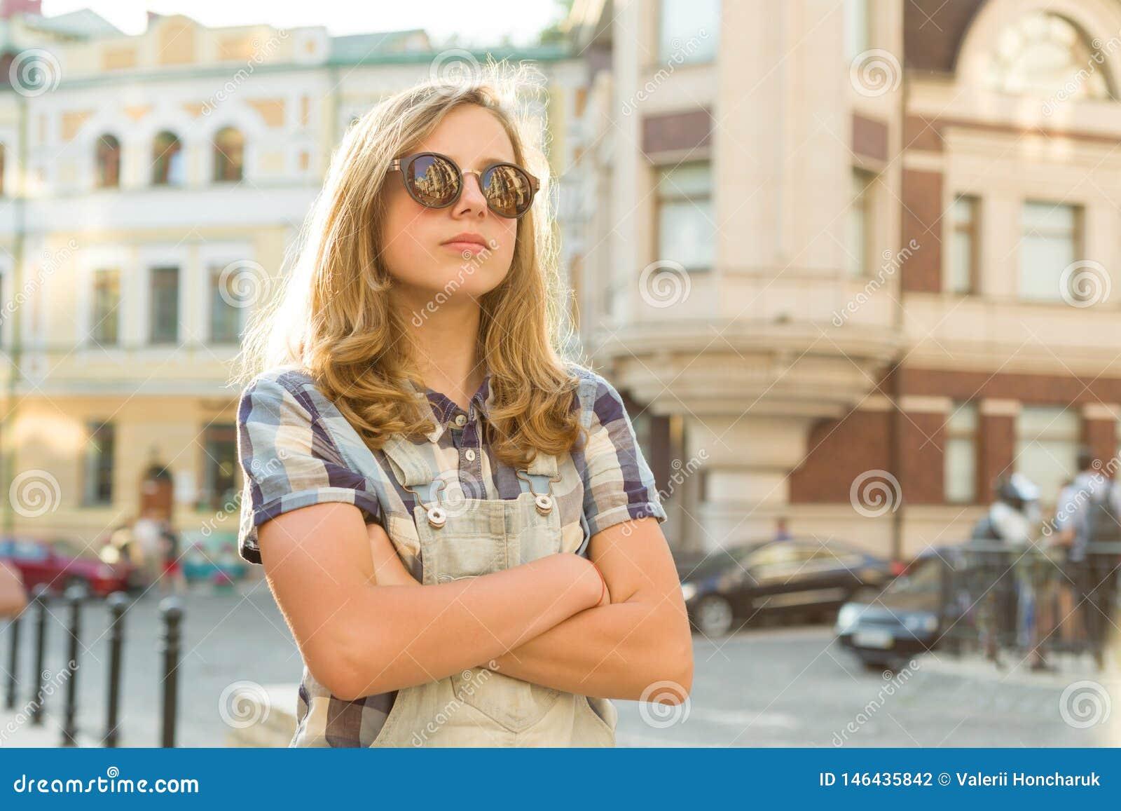 Stående av den ledsna olyckliga tonåriga flickan med vikta händer på stadsgatan, kopieringsutrymme