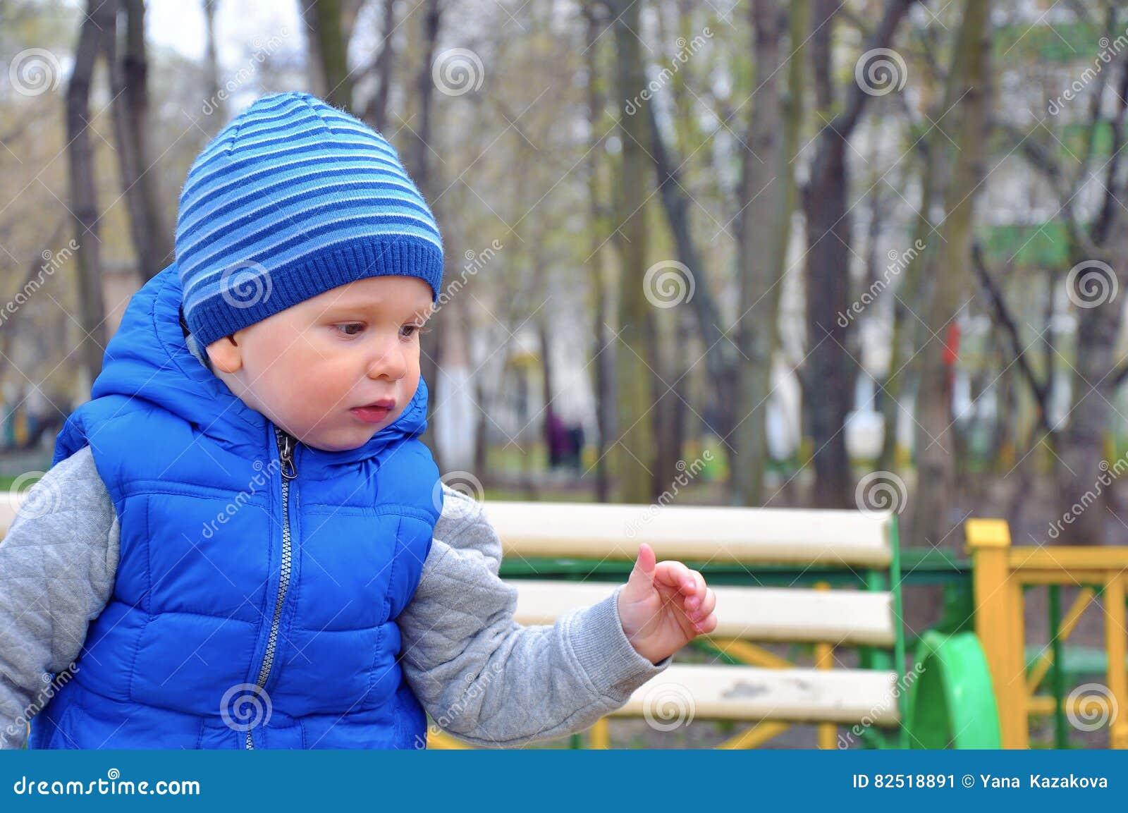 Stående av den lilla trevliga pojken i ett lock i den tidiga våren