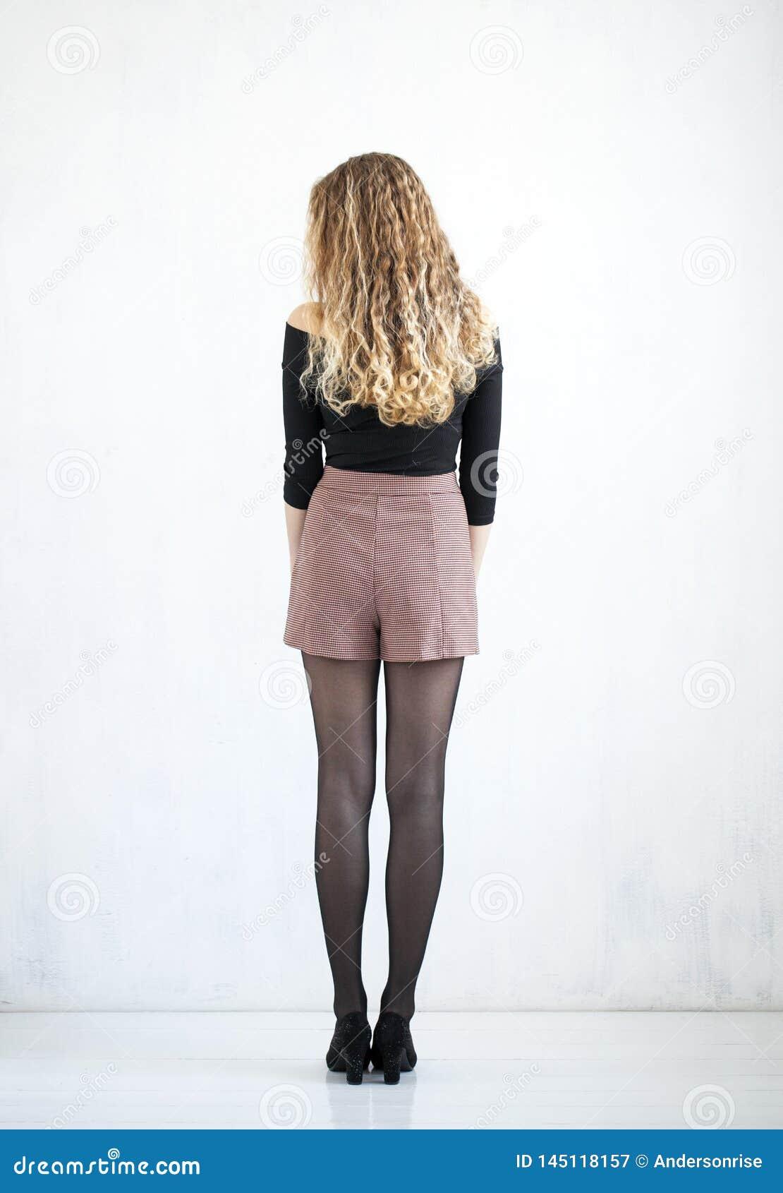 Stående av den lockiga blondinen för full längd i en svart blus och en kort kjol
