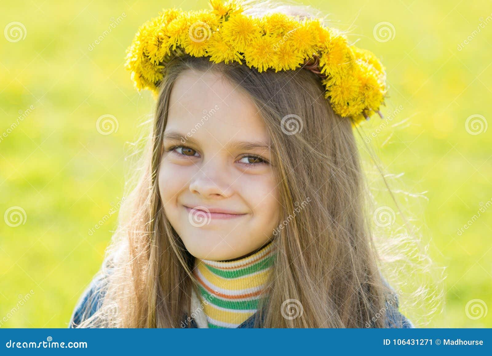 Stående av den lyckliga åtta-år-gamla flickan med en krans av maskrosor på hennes huvud, mot bakgrunden av en vårröjning